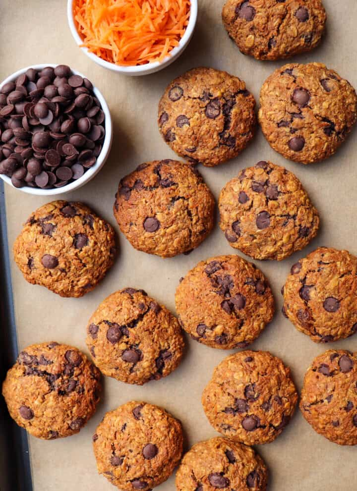 Cookies on baking tray with mini chocolate chocolate chips and grated carrot in mini bowls for decoration.