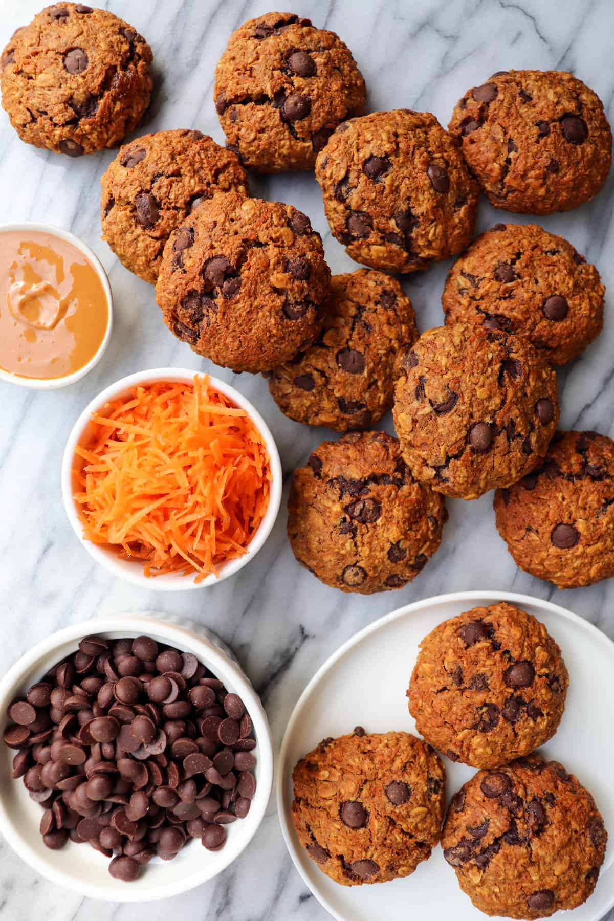 Carrot cookies on marble slab with mini bowls of grated carrot, chocolate chips and peanut butter on the side for decoration.