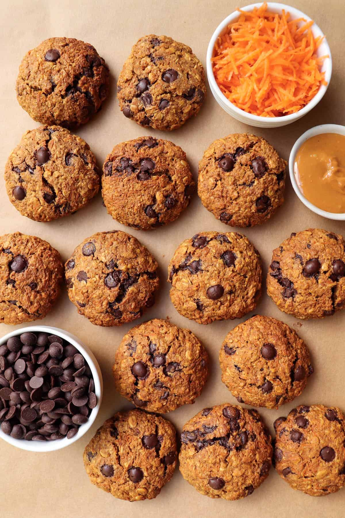 Chocolate chip cookies on baking paper. Side dish of grated carrots, chocolate chips and peanut butter for decoration.