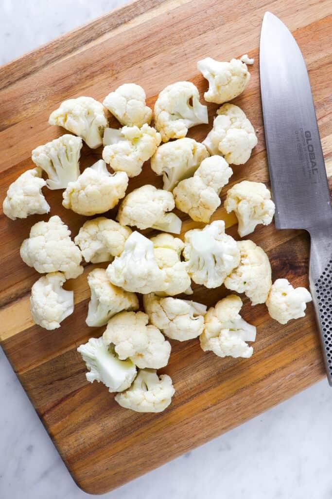 Raw chopped cauliflower florets on cutting board with knife.