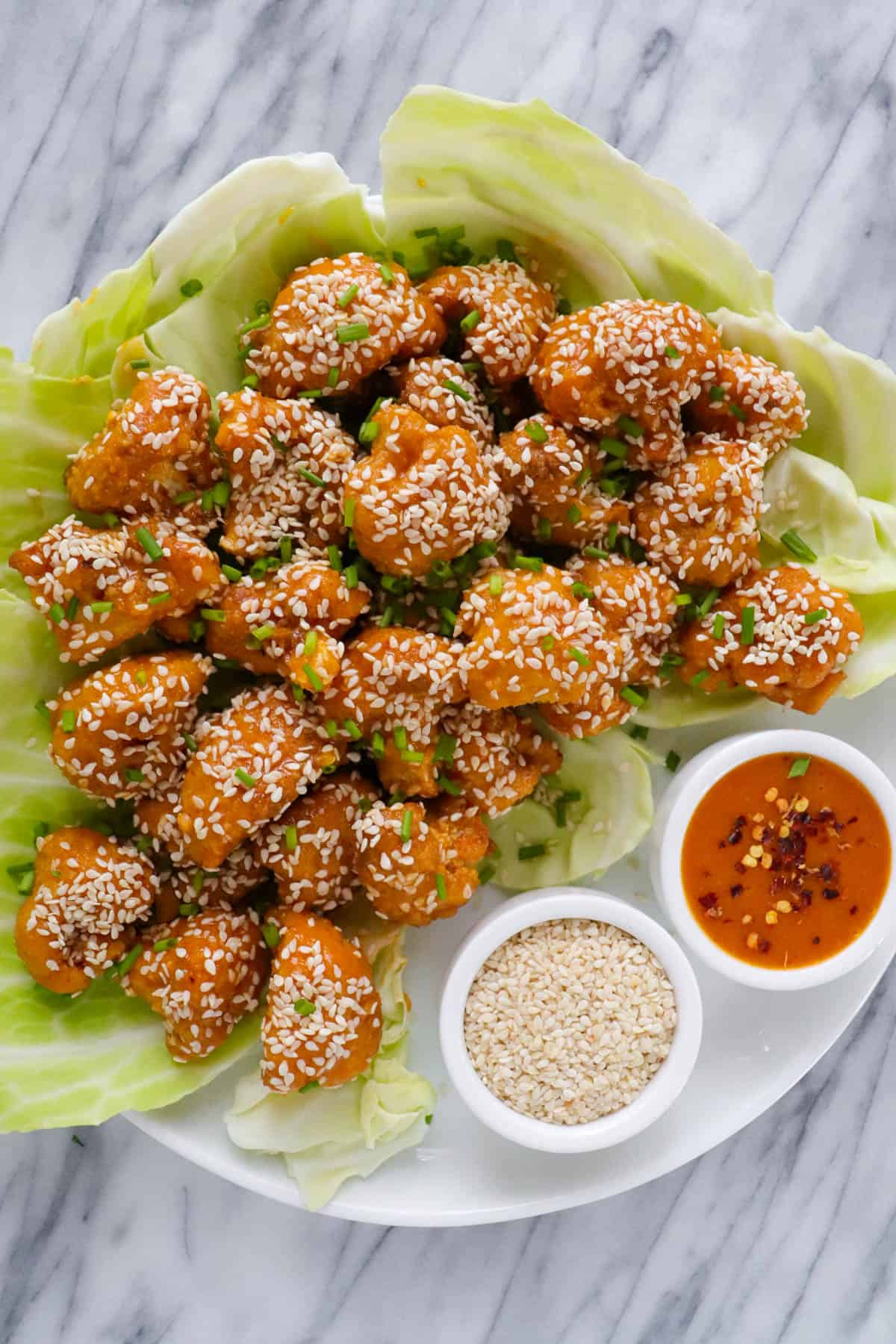 Baked cauliflower wings on plate with sesame seeds and extra sauce.