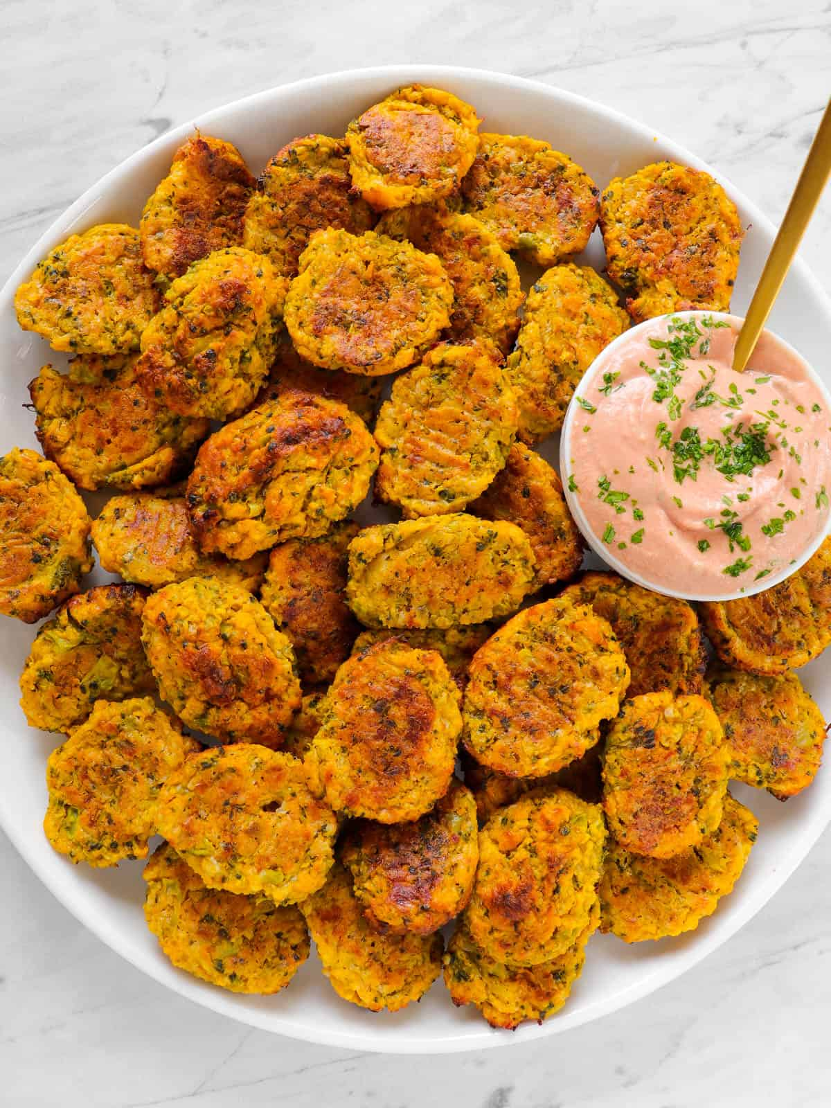 Baked broccoli pumpkin tots on a plate with tomato yoghurt sauce and golden spoon.