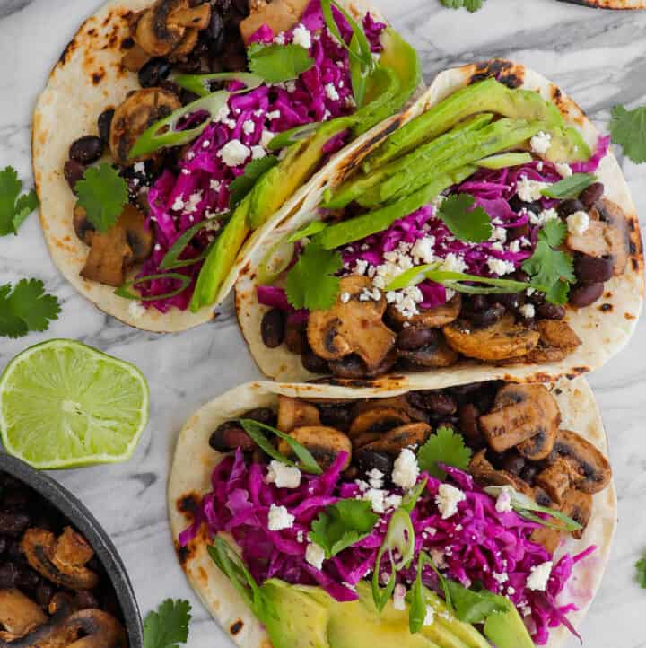 Close up shot of tacos with avocado, lime and mushroom mixture on side for decoration.