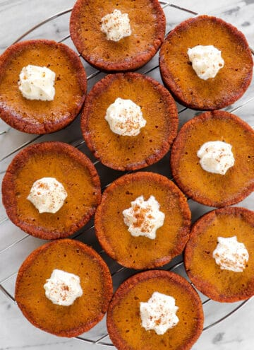 Baked pumpkin pies with whipped cream on top.
