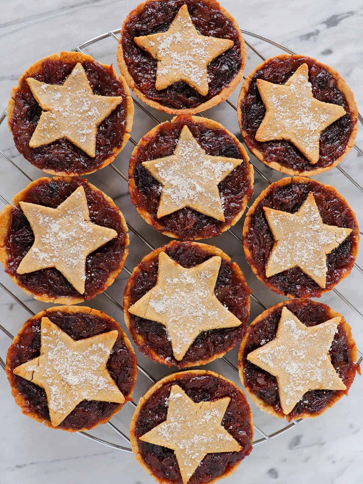 Baked fruit mince pies on cooling rack.