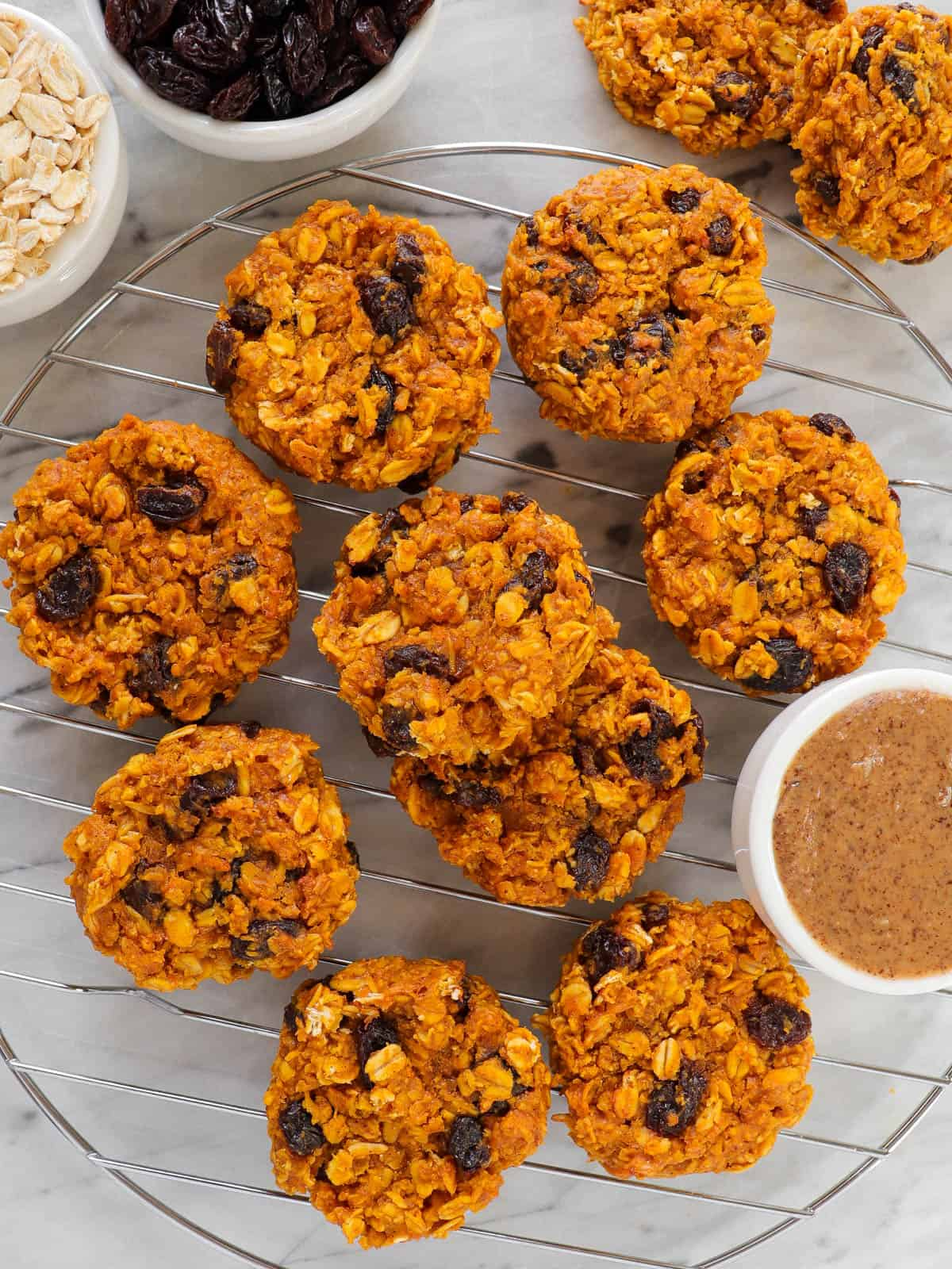 Sweet potato cookies on cooling rack with nut butter, oats and raisins in mini bowls on the side.