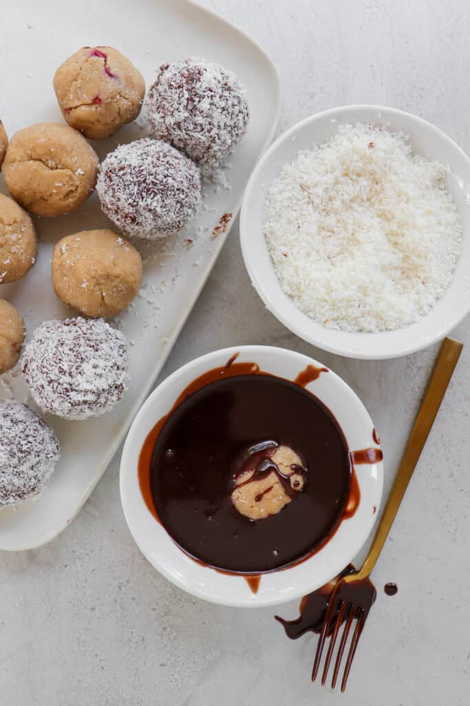 Lamington balls getting dipped in chocolate and coated in chocolate.