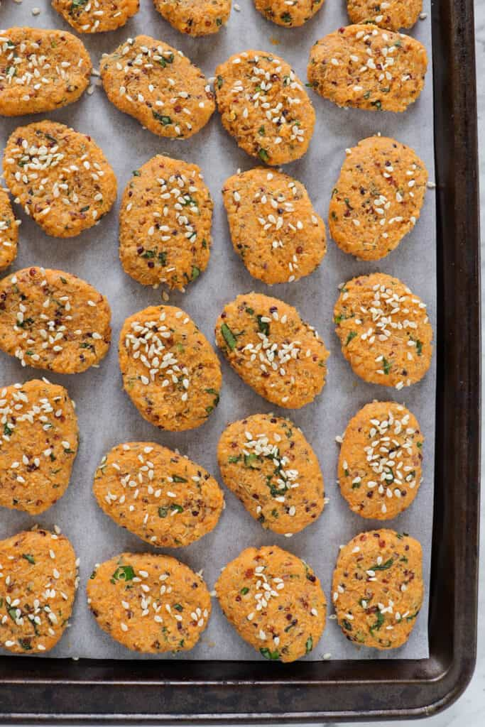 Unbaked sweet potato bites on baking tray with sesame seeds sprinkled on top.