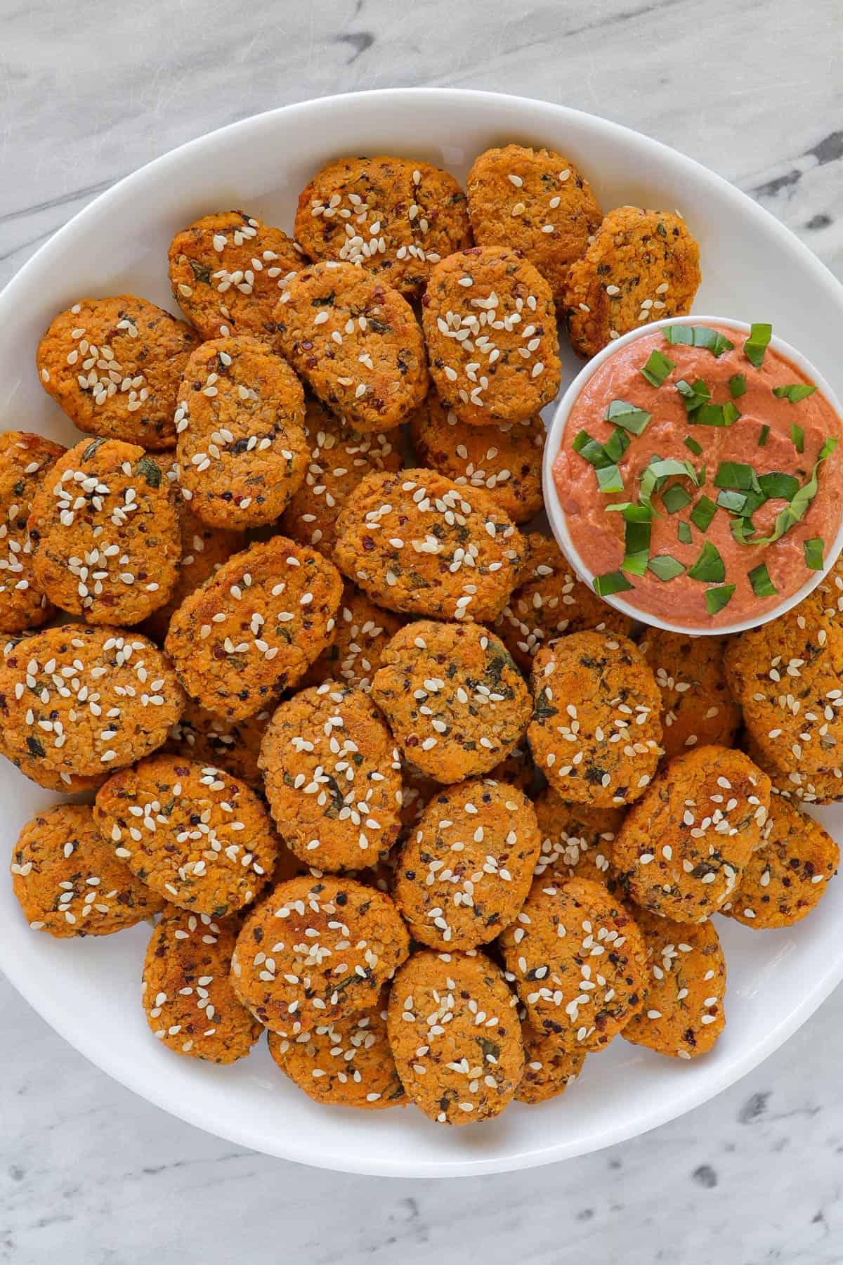 Sweet potato bites on round plate with creamy tomato dip.