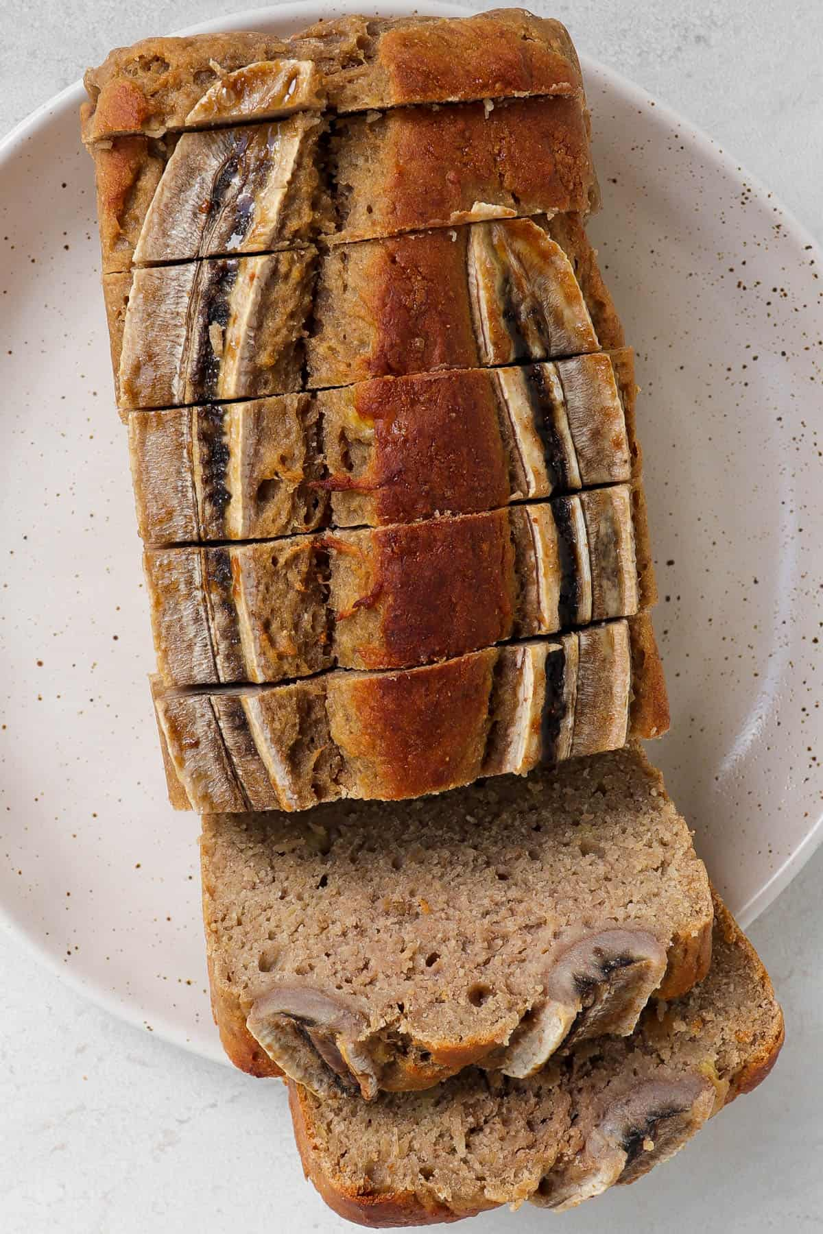 Sliced up buckwheat bread on plate with two slices opened up.