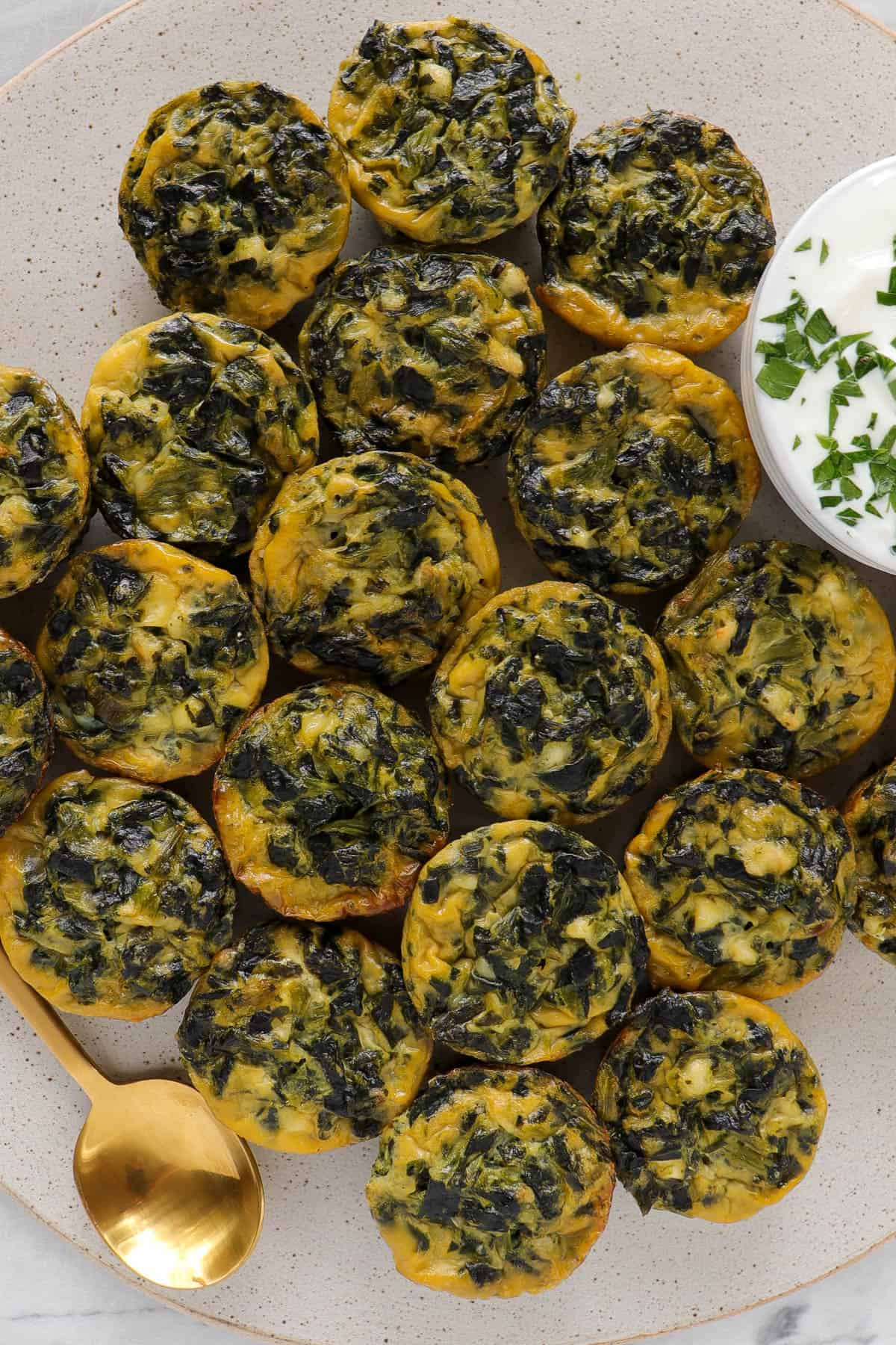 Mini spinach and feta quiche on big plate with yoghurt topping sauce and gold spoon for decoration.