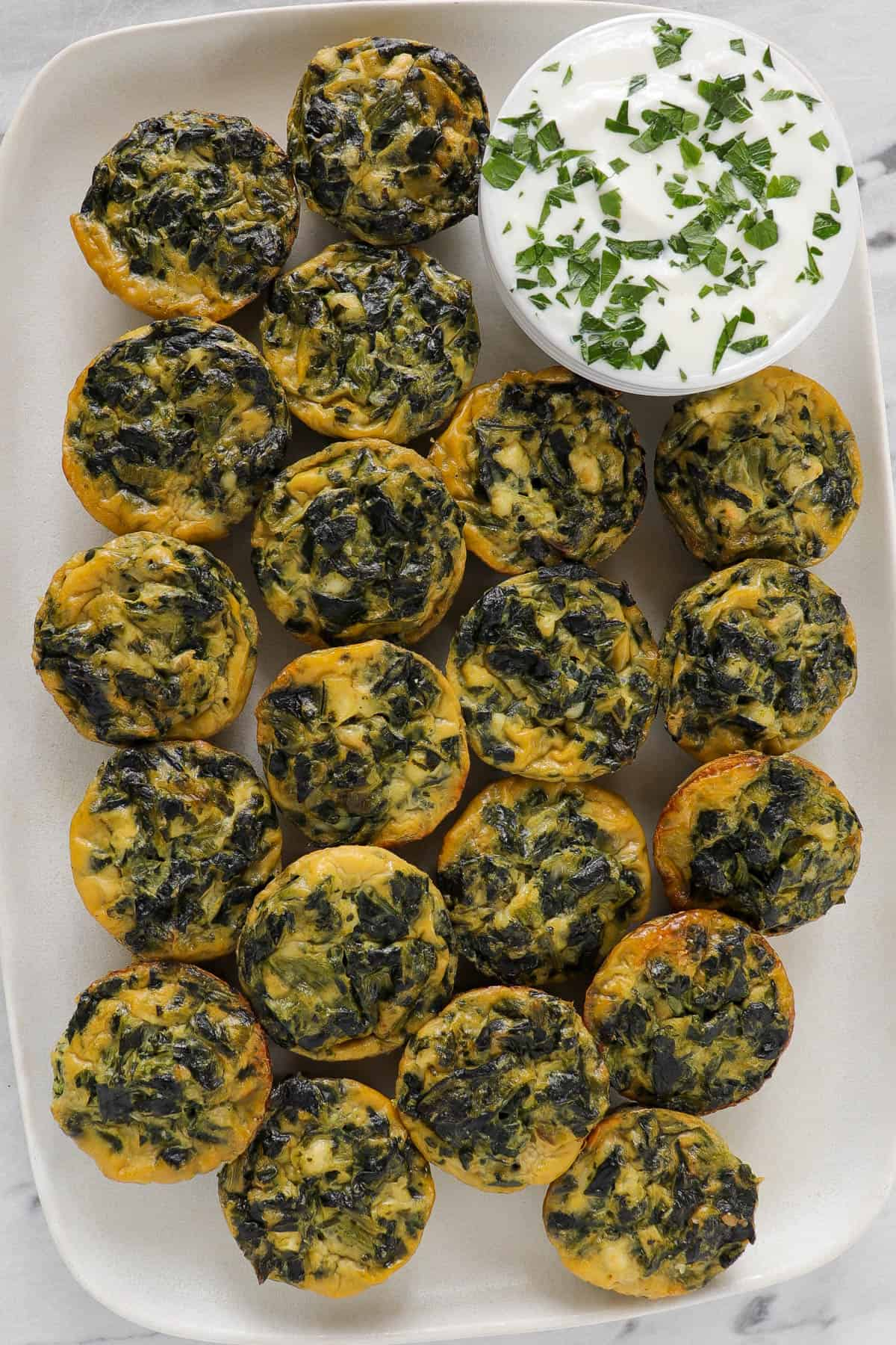 Mini spinach and feta quiche on platter with yoghurt topping sauce.