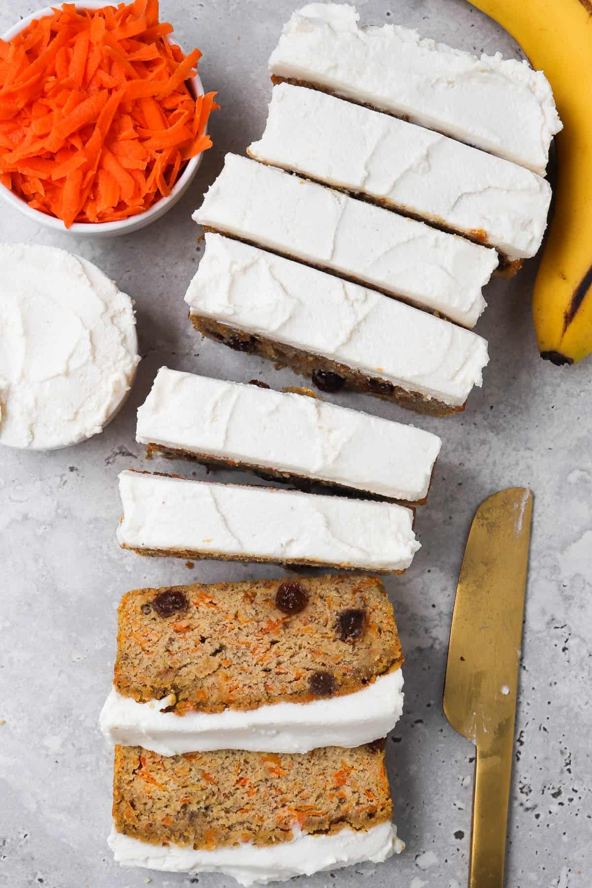 Sliced up frosted bread with frosting, carrot, banana and gold knife on the side for garnish.