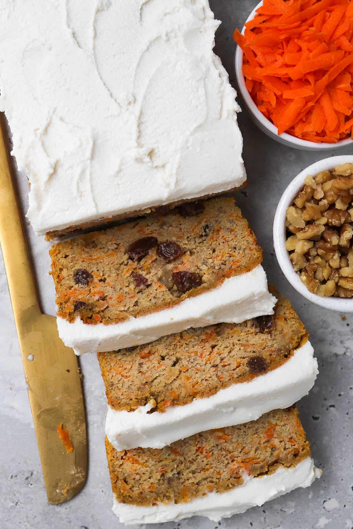 Sliced up frosted bread with walnuts, carrot and gold knife on the side for garnish.