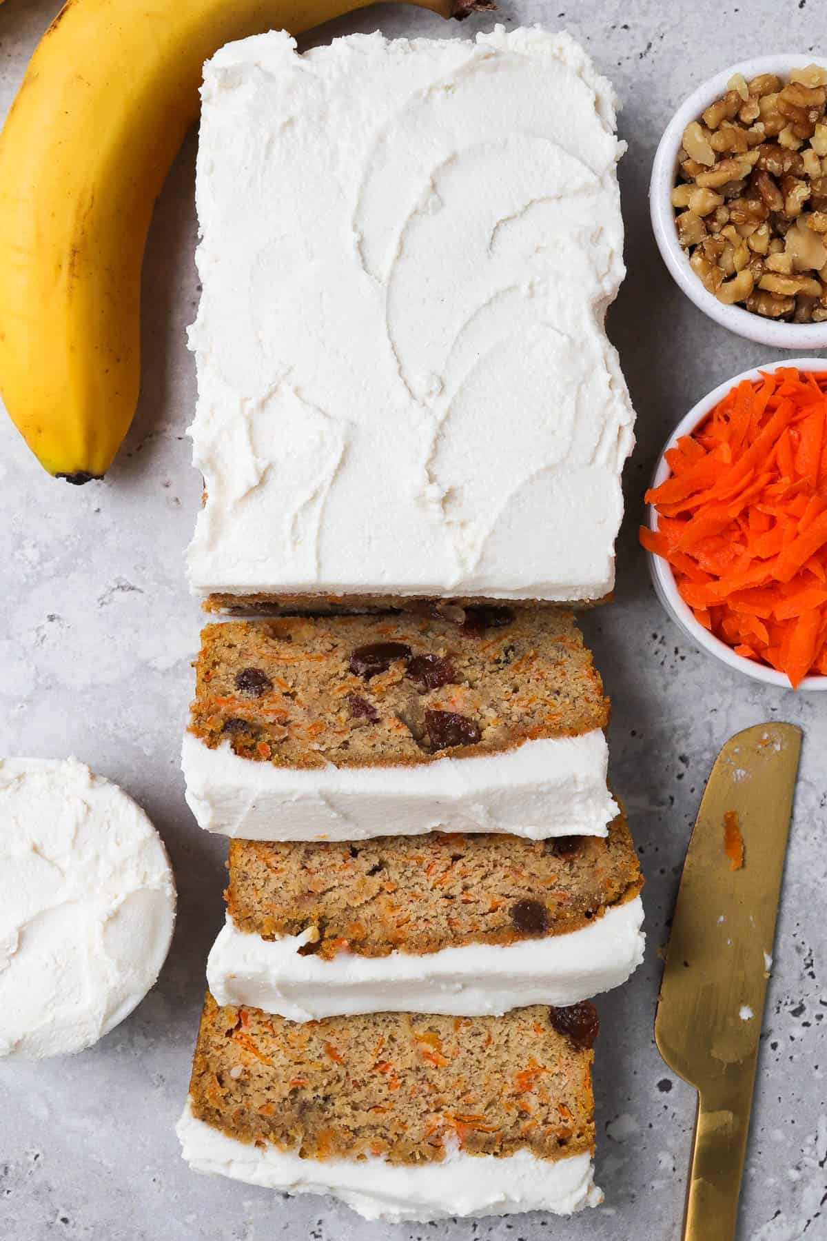 Bread topped with frosting cut into there slices at front. Small dish of grated carrot, walnuts, frosting, banana and gold knife on the side for garnish.