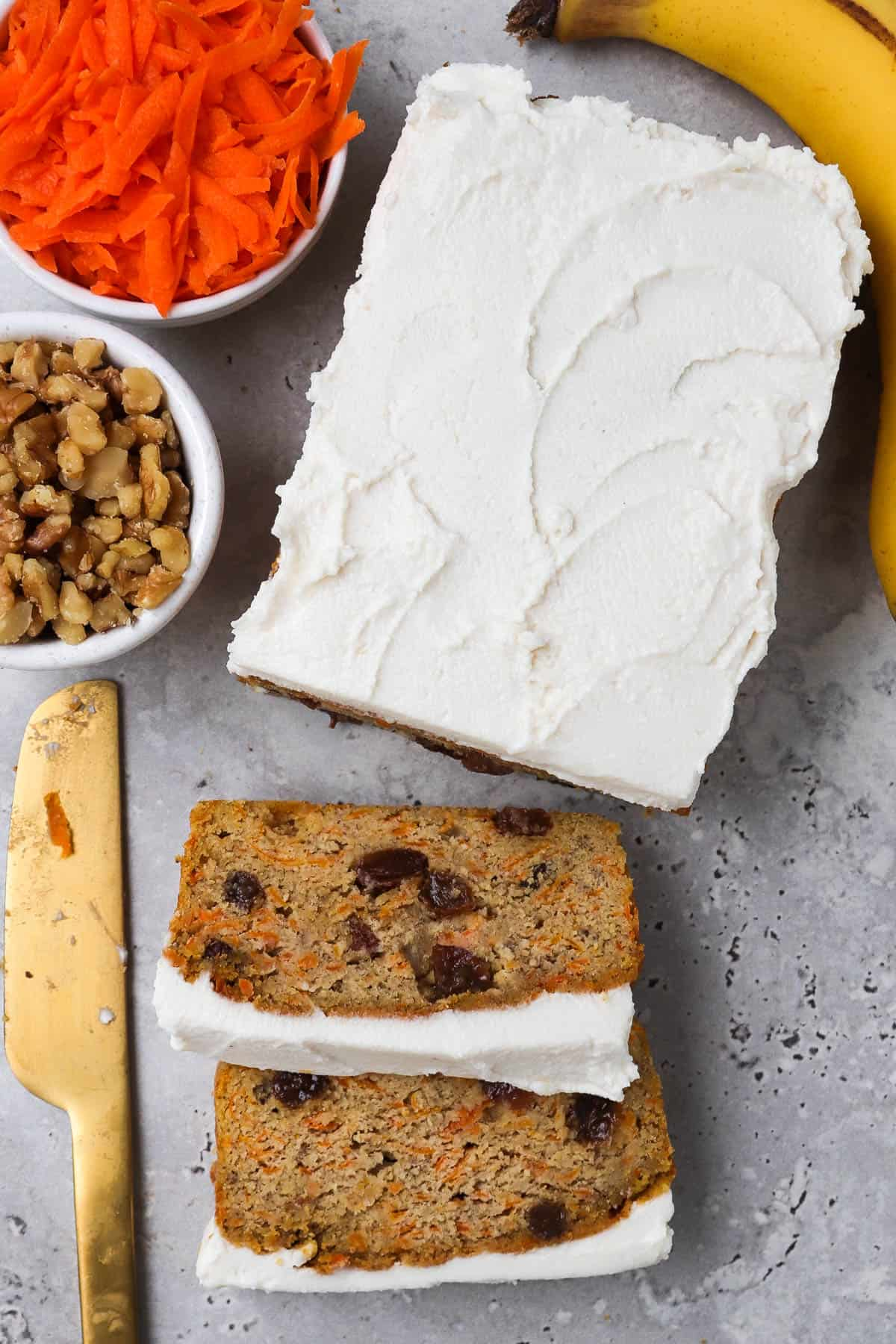 Bread topped with frosting cut into there slices at front. Small dish of grated carrot, walnuts, banana and gold knife on the side for garnish.