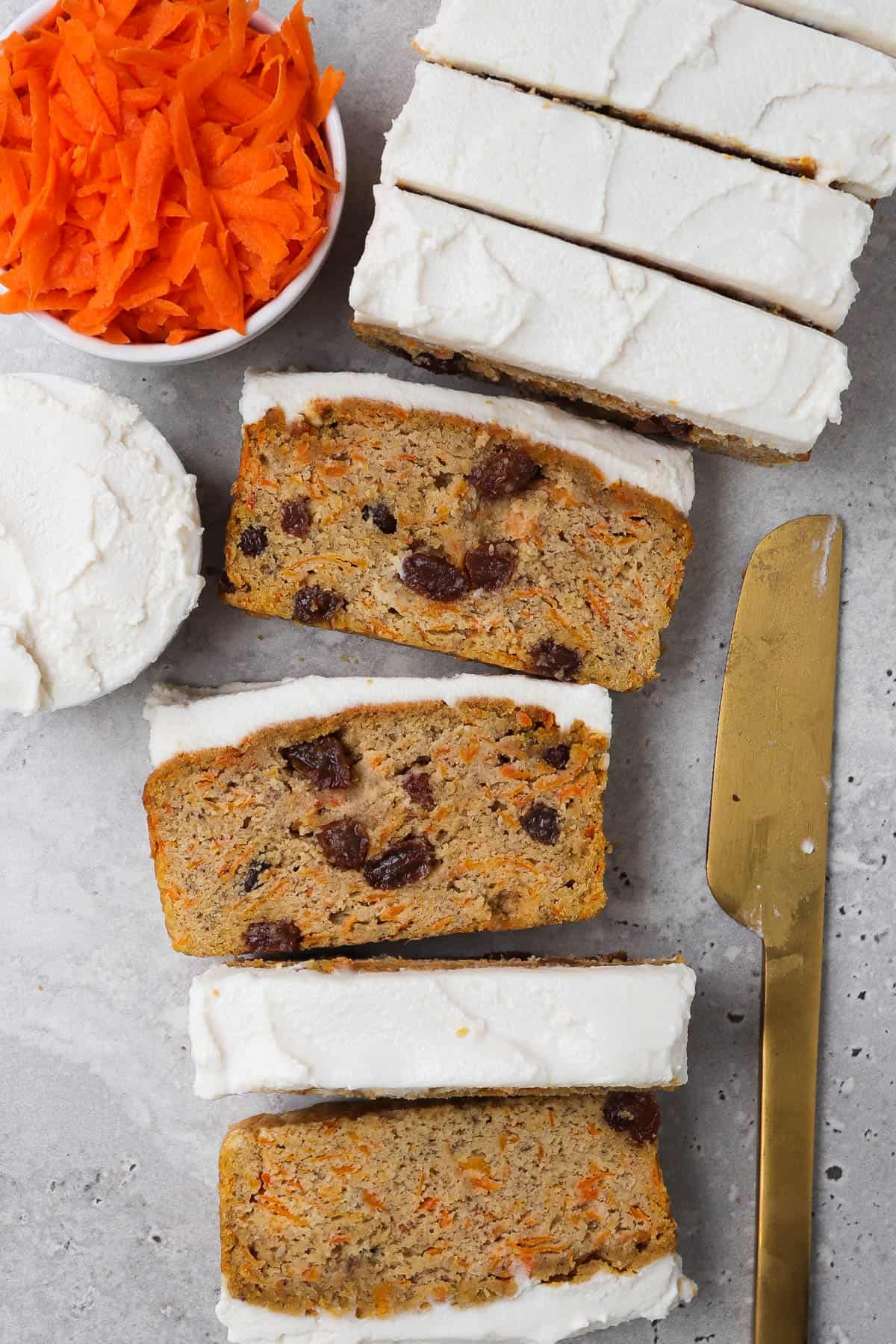 Sliced up frosted bread with grated carrot, frosting and gold knife on the side for garnish.