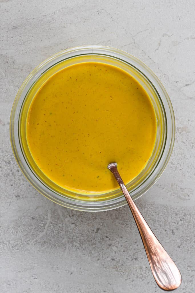Cheesy tahini sauce in a jar with a spoon.