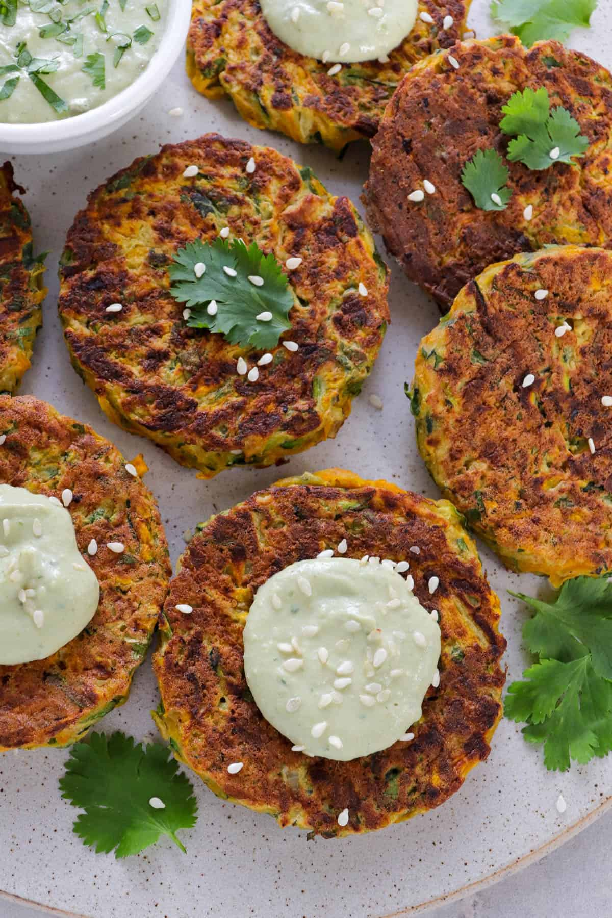 Close up shot of fritters with coriander leaves, avocado dip dolloped on top and sprinkled with sesame seeds.
