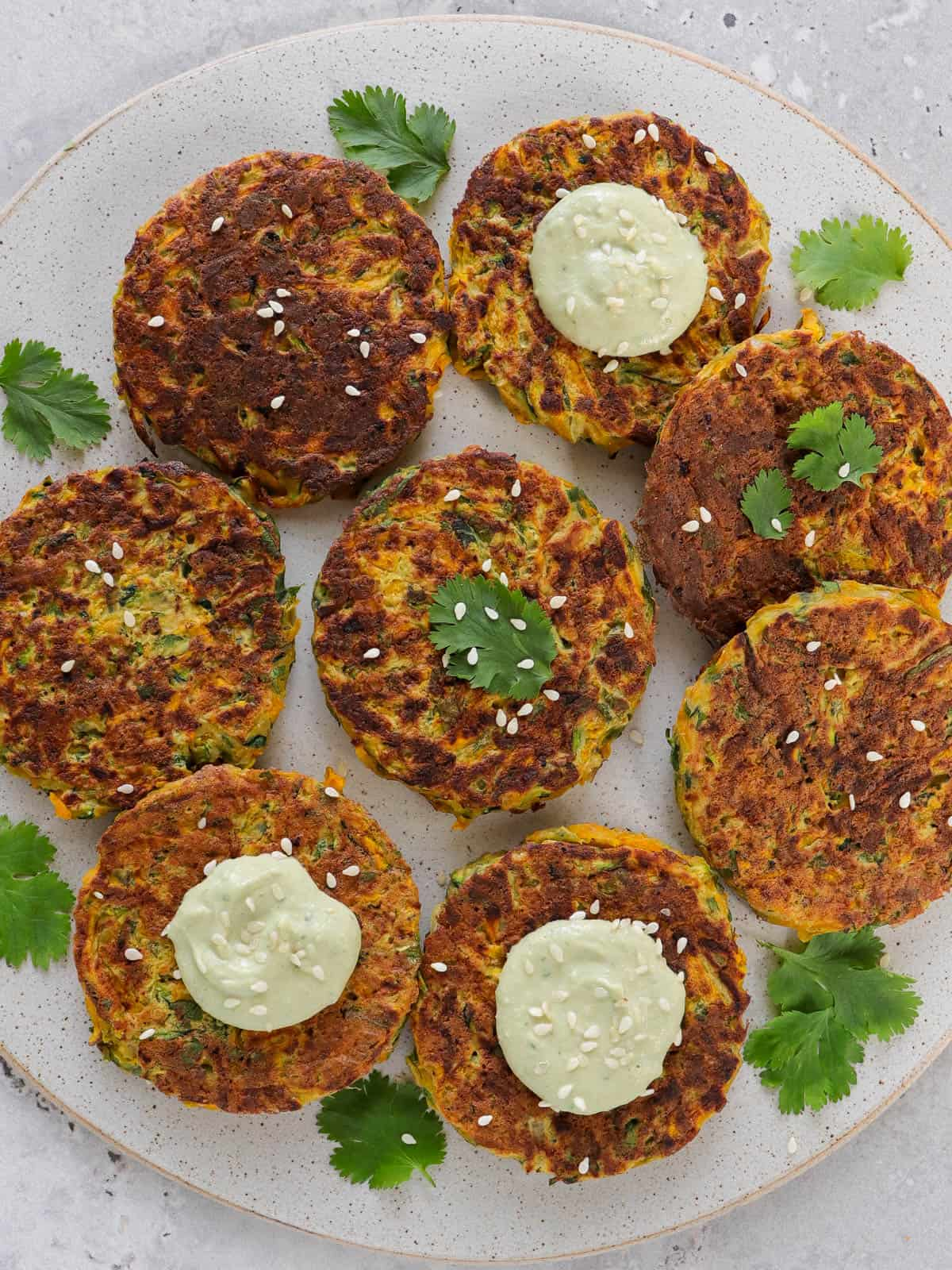 Cooked fritters on a plate with coriander leaves, avocado dip dolloped on top and sprinkled with sesame seeds.