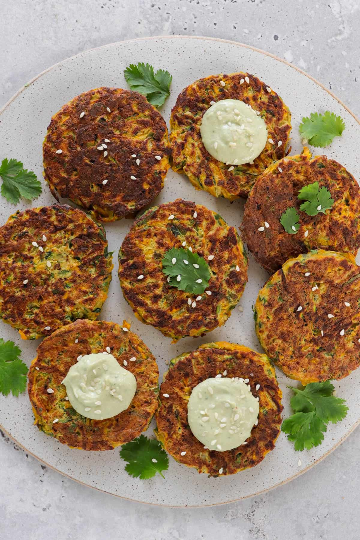 Cooked patties on a plate with coriander leaves, avocado dip dolloped on top and sprinkled with sesame seeds.