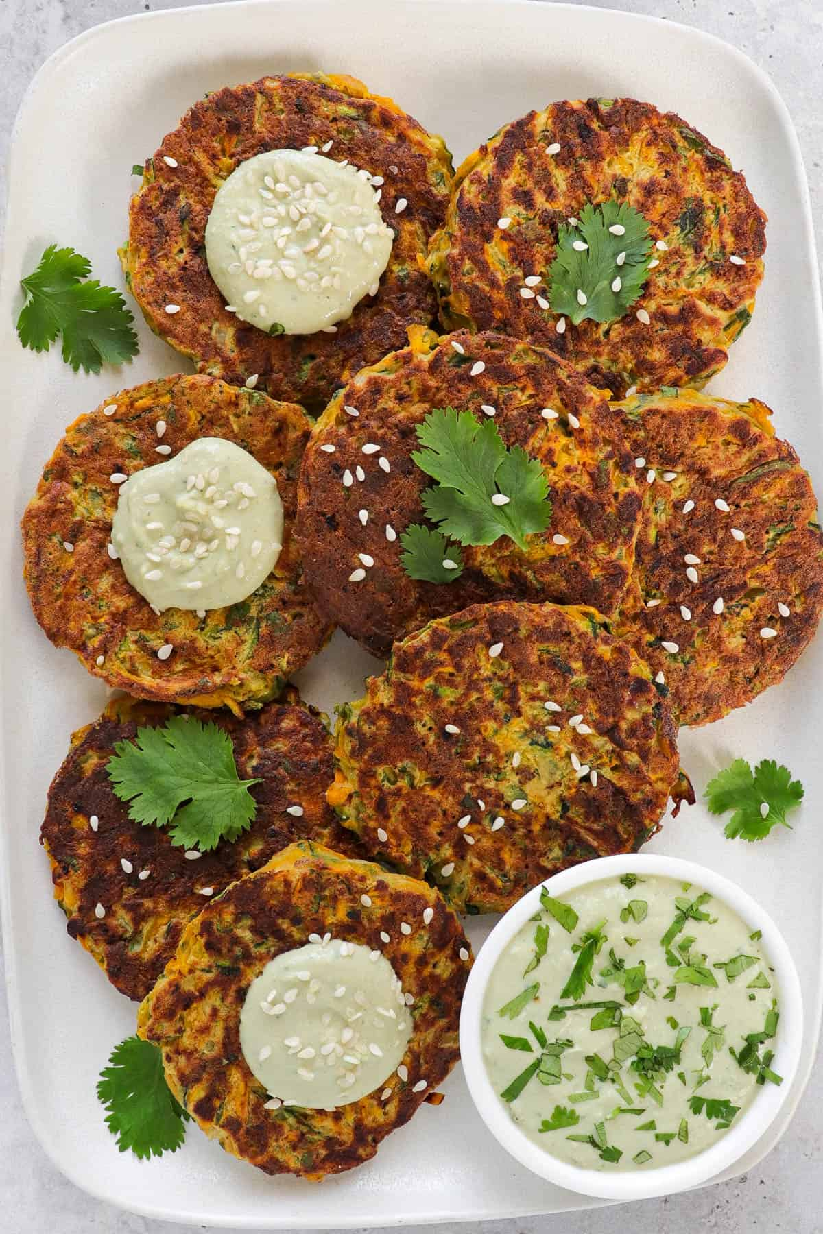 Fritters on a rectangle plate with coriander leaves, sesame seeds and avocado dip on the side.