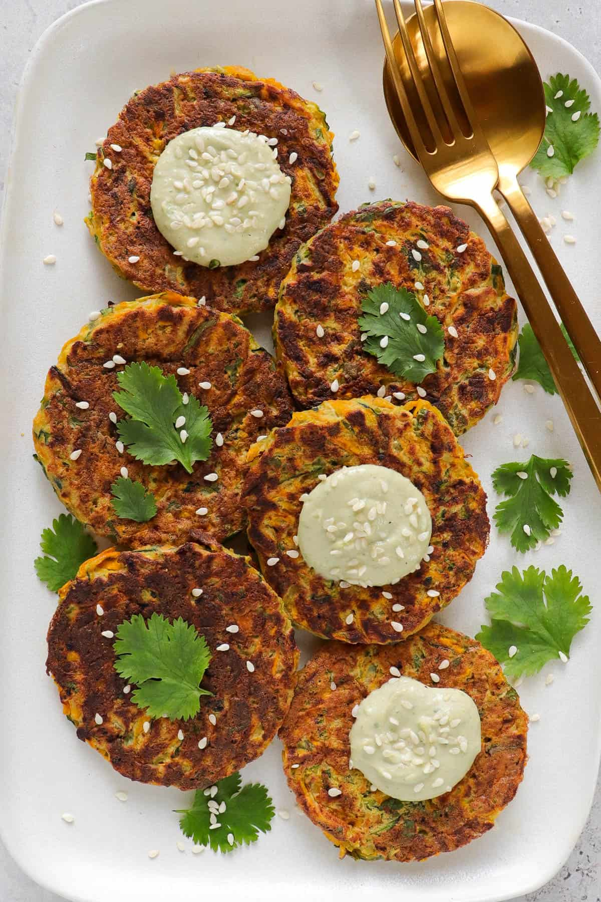 Patties on a rectangle plate with coriander leaves, sesame seeds, avocado dip and gold cutlery on the side.