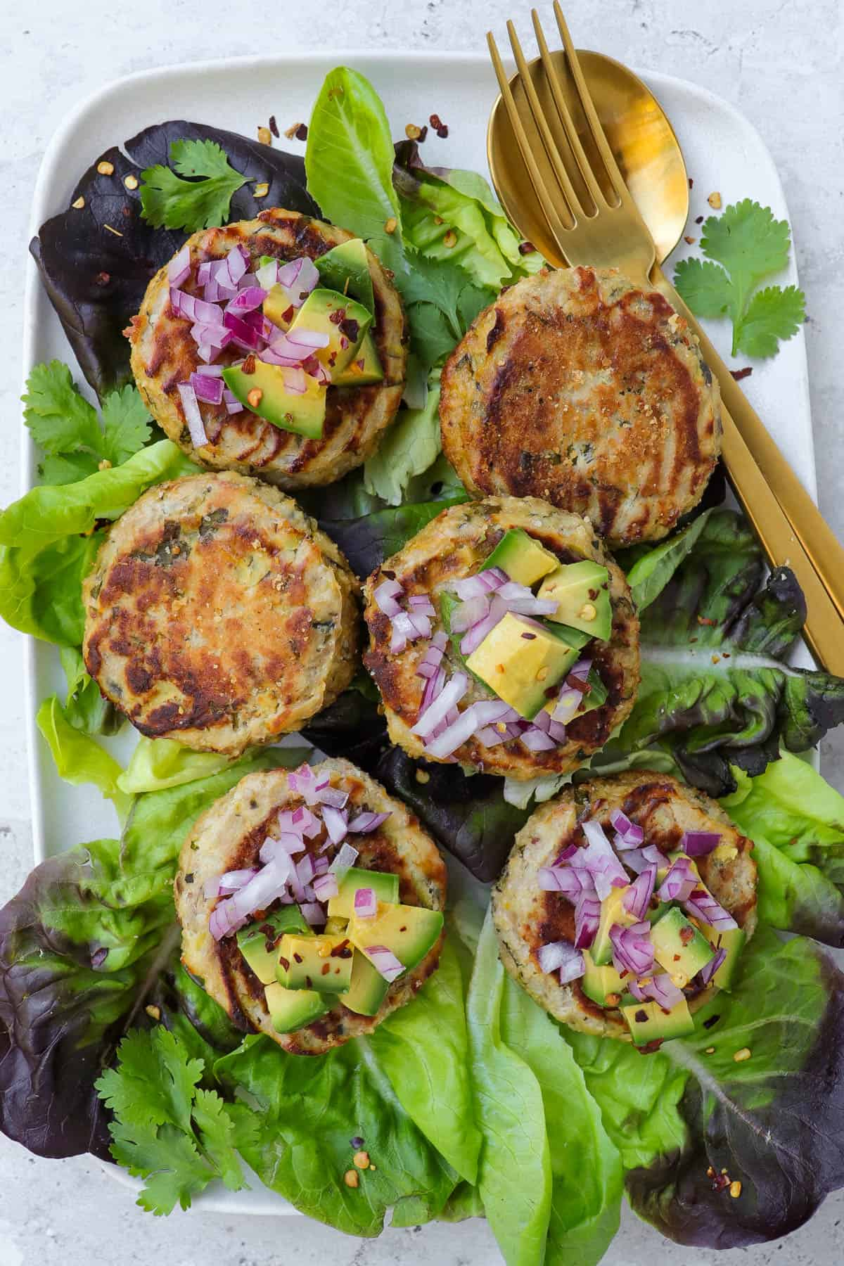 Tuna cakes on lettuce leaves with chopped avocado, red onion and chili flakes on top of each one. Gold cutlery on the side.