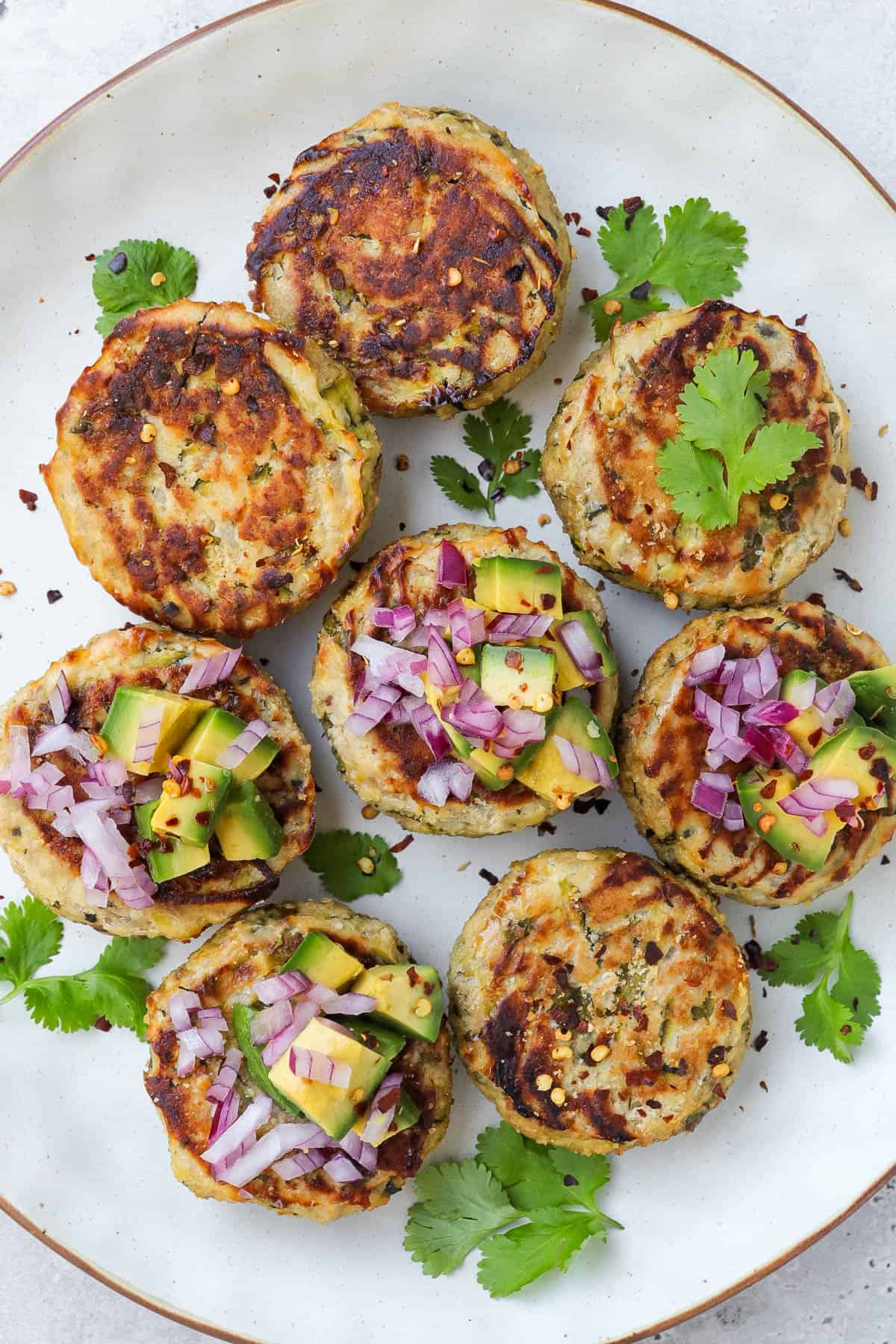 Tuna cakes on plate with chopped avocado, red onion and chili flakes on top of each one. Fresh coriander leaves to decorate.