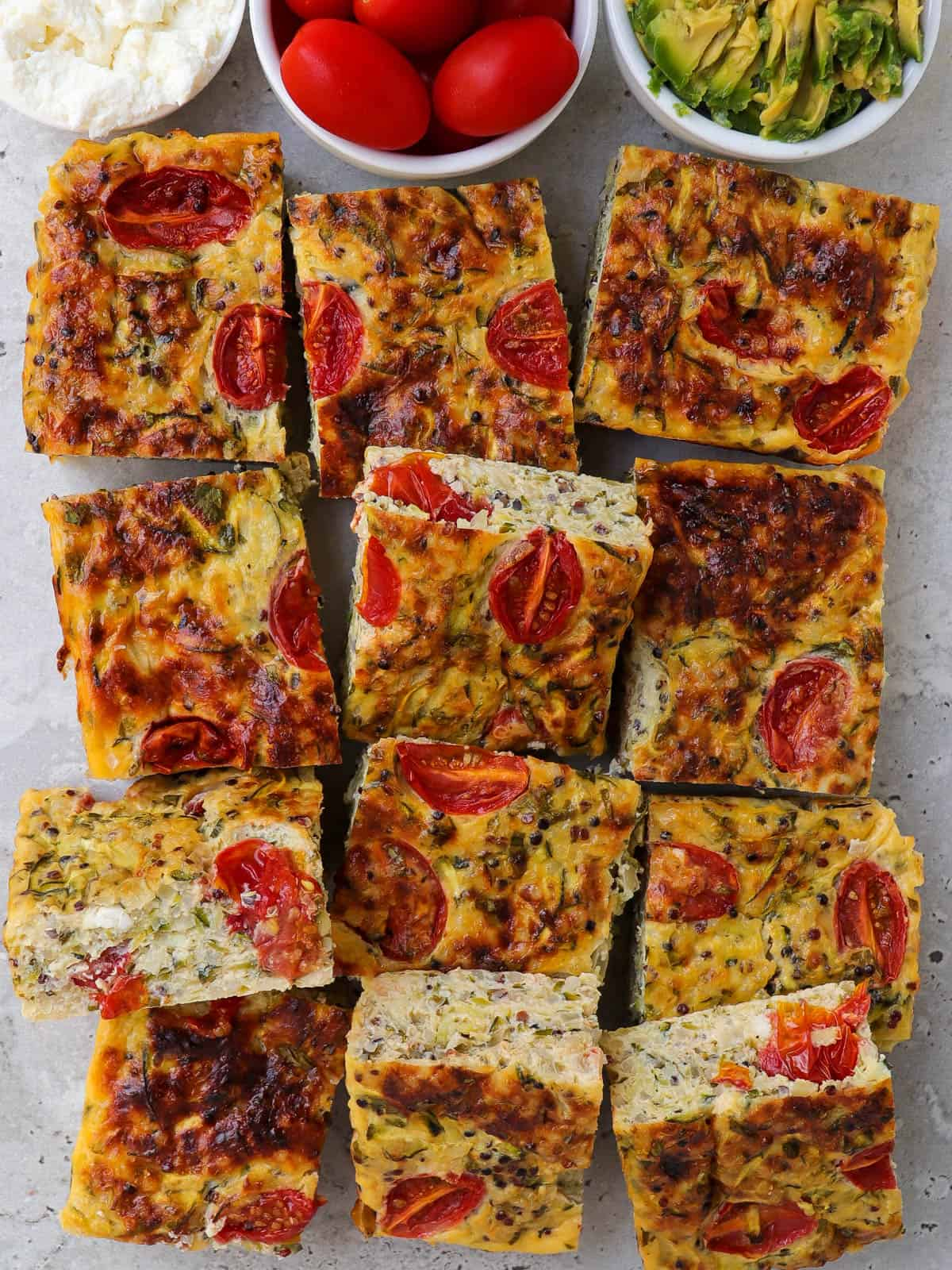 Cooked zucchini slice. Small dishes of cottage cheese, cherry tomatoes and mashed avocado on the top side for decoration.