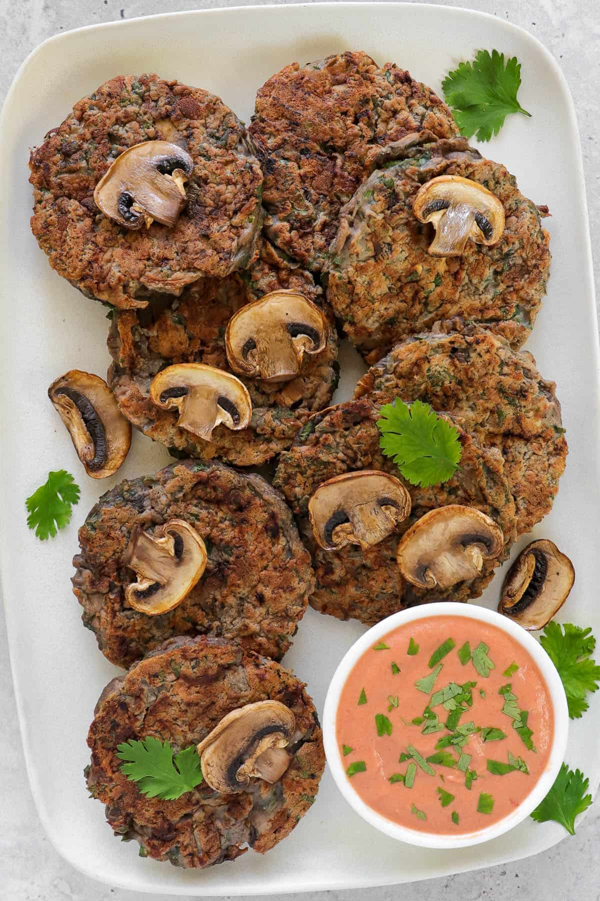 Fritter on rectangle plate. cooked mushrooms and coriander leaves on top of fritters for decoration. Creamy tomato sauce on the side.