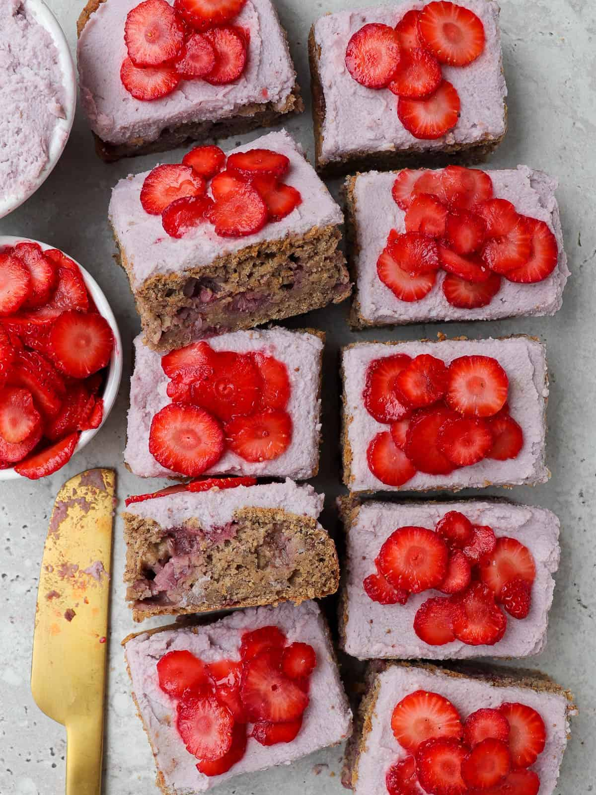 Frosted cake topped with sliced strawberries and cut up into small rectangle slices. two slices tilted on the side or an inside view.