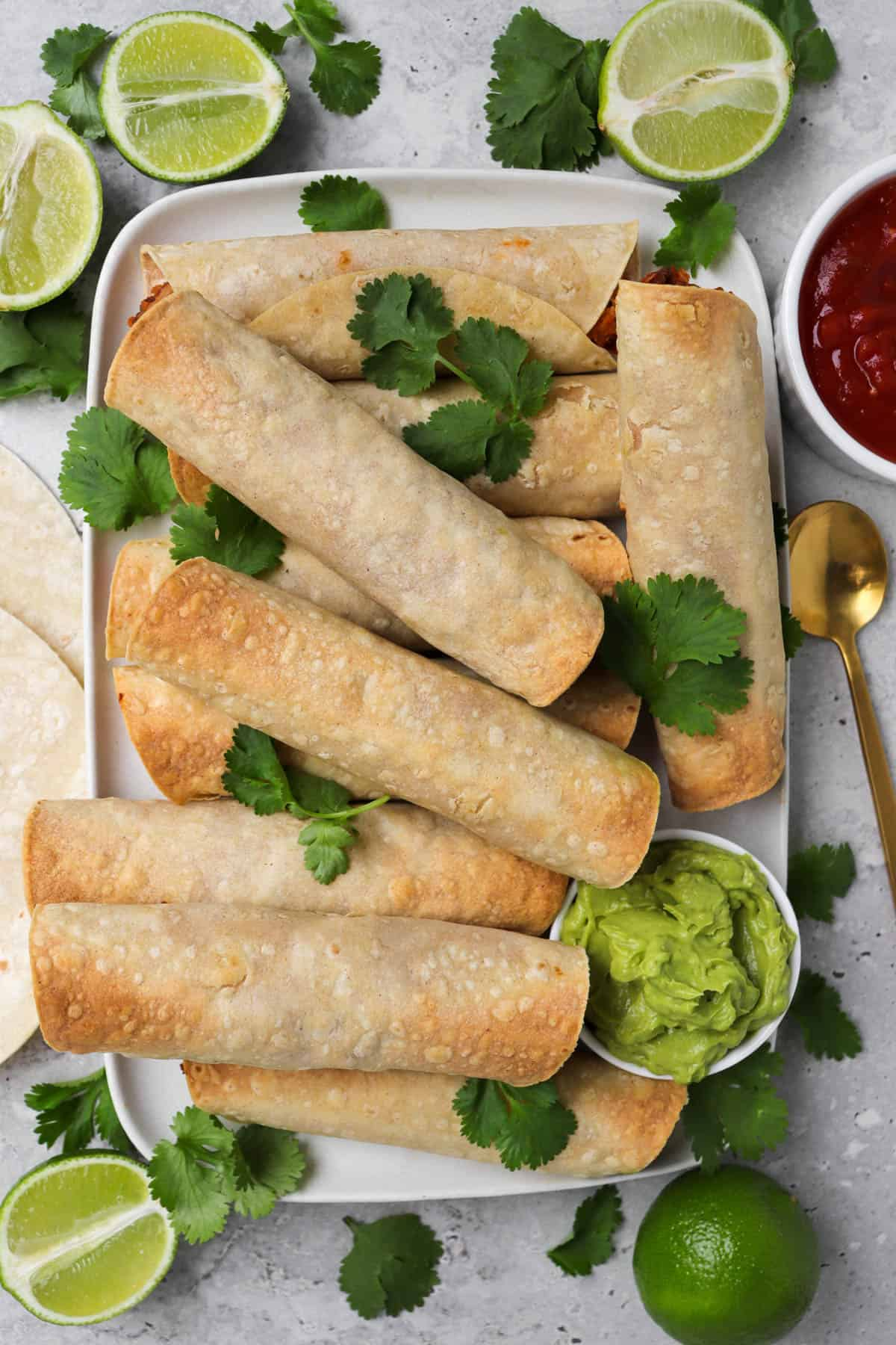 Taquitos on a platter garnished with coriander, side of guacamole, halved limes, gold spoon and salsa on the side.