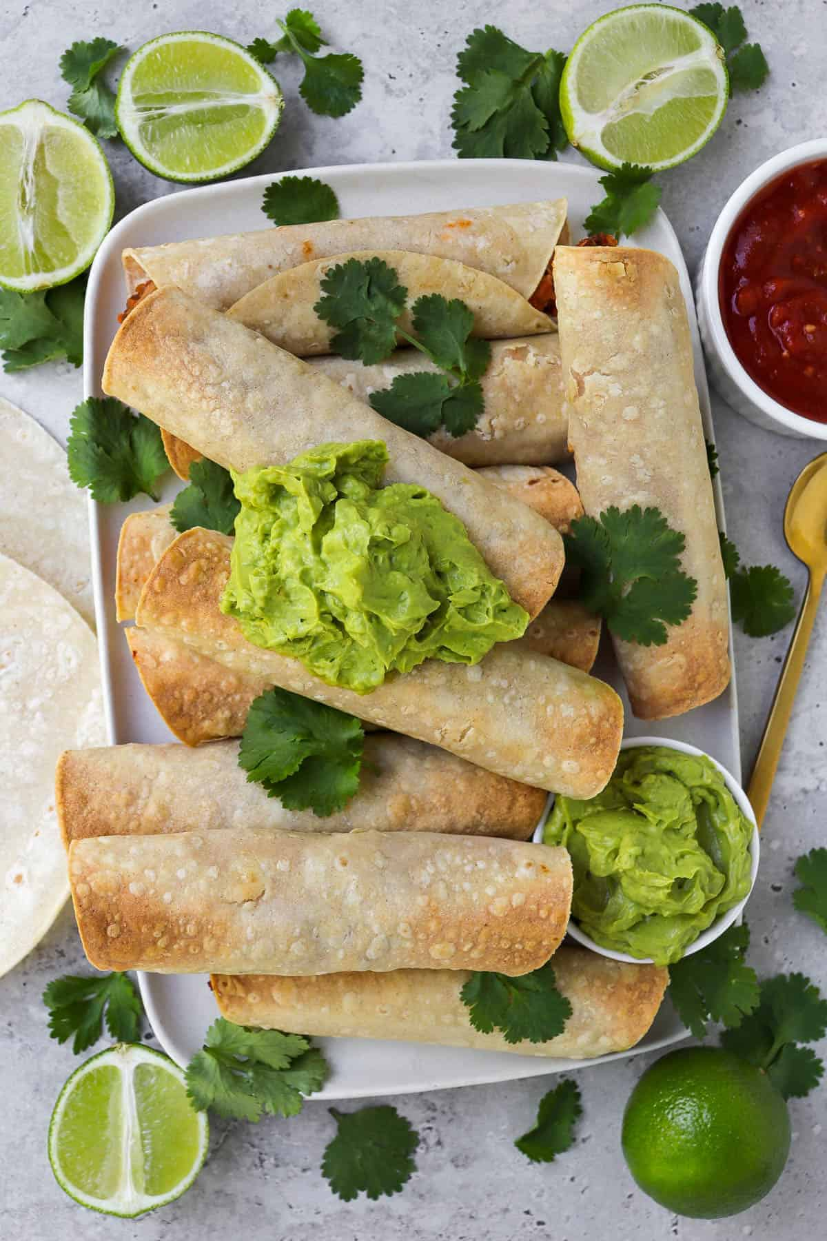 Taquitos on platter topped with coriander leaves and guacamole. Fresh cut up limes, tortillas, salsa and gold spoon on the sides.