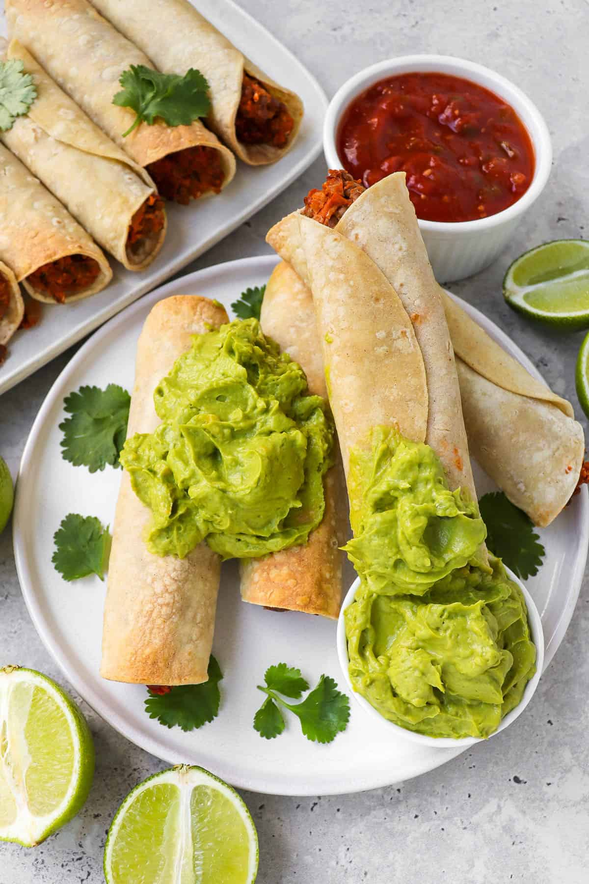 Taquitos on a plate dipped in the guacamole.