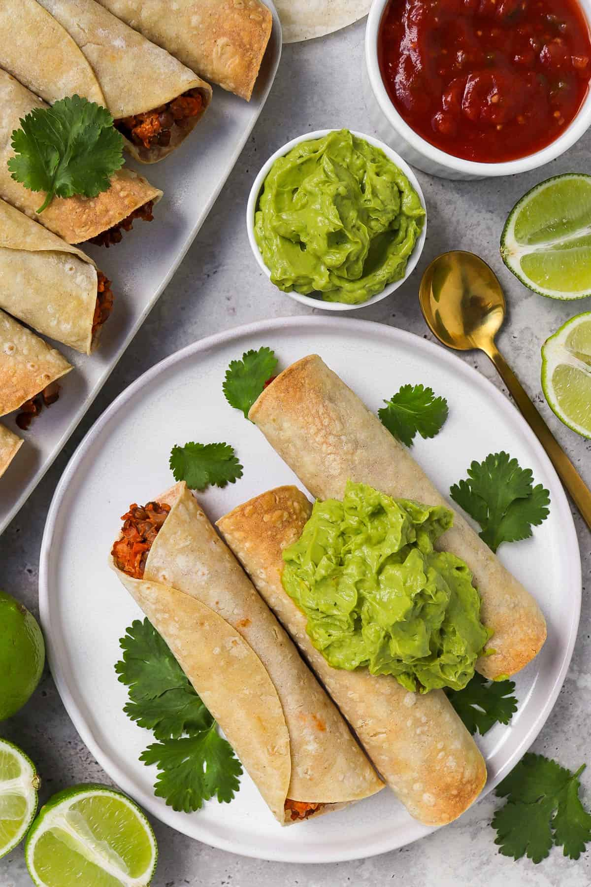 Taquitos served on plate on the side topped with guacamole.