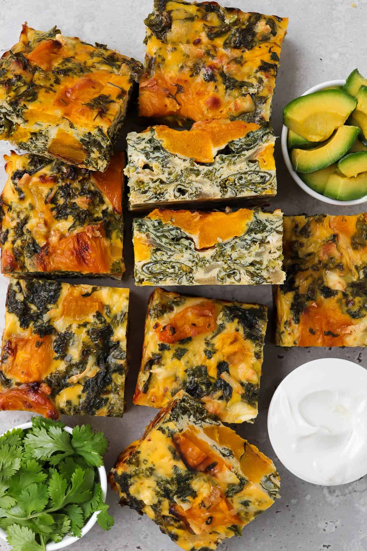 Frittata cut into slices. Avocado, coriander leaves and yoghurt on the side for garnish.