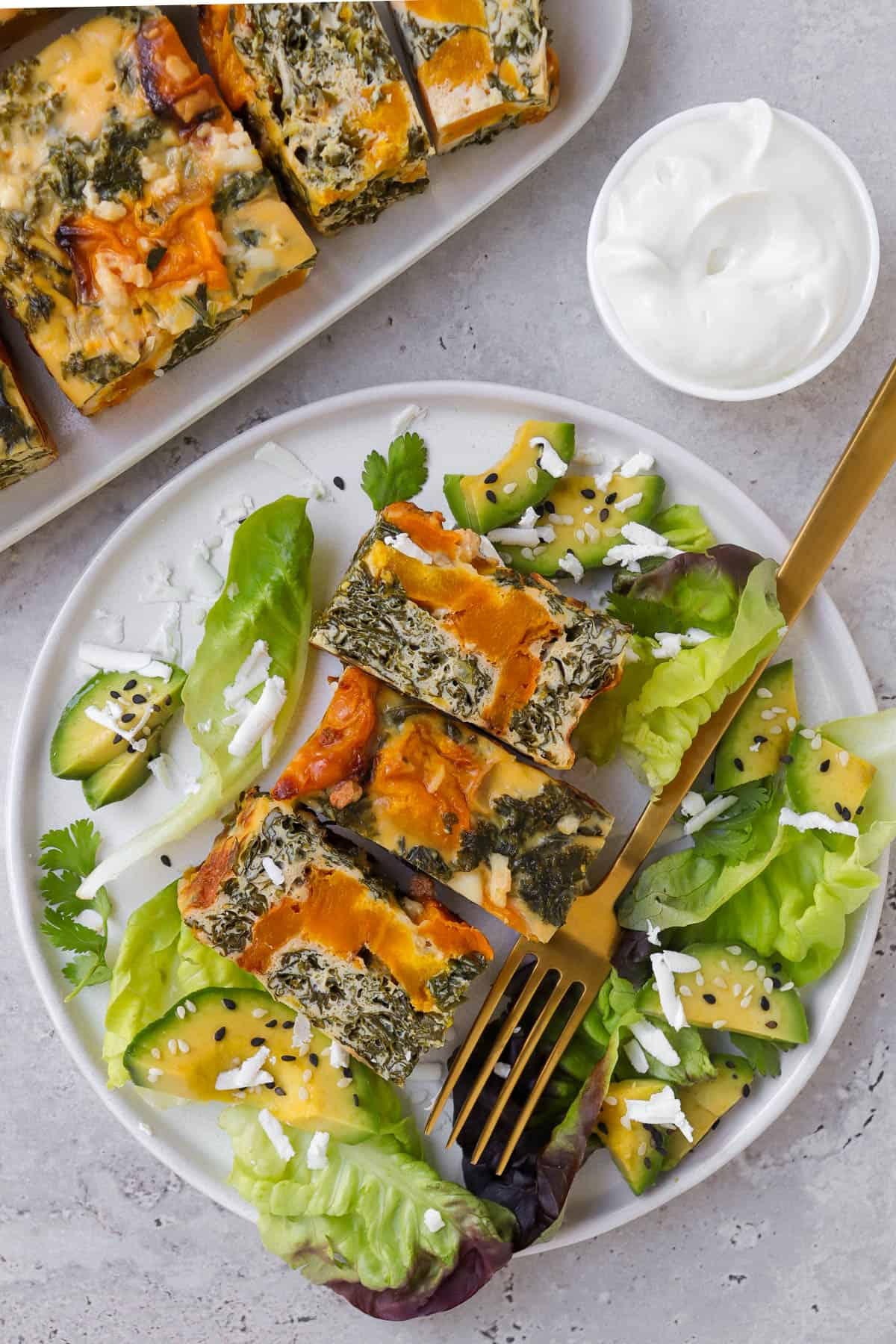 Sliced frittata on plate with lettuce, feta, avocado and gold fork.