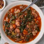 Soup in a bowl with spoon. Buckwheat bread, dried lentils, sprig of parsley, chili flakes on the side for decoration.