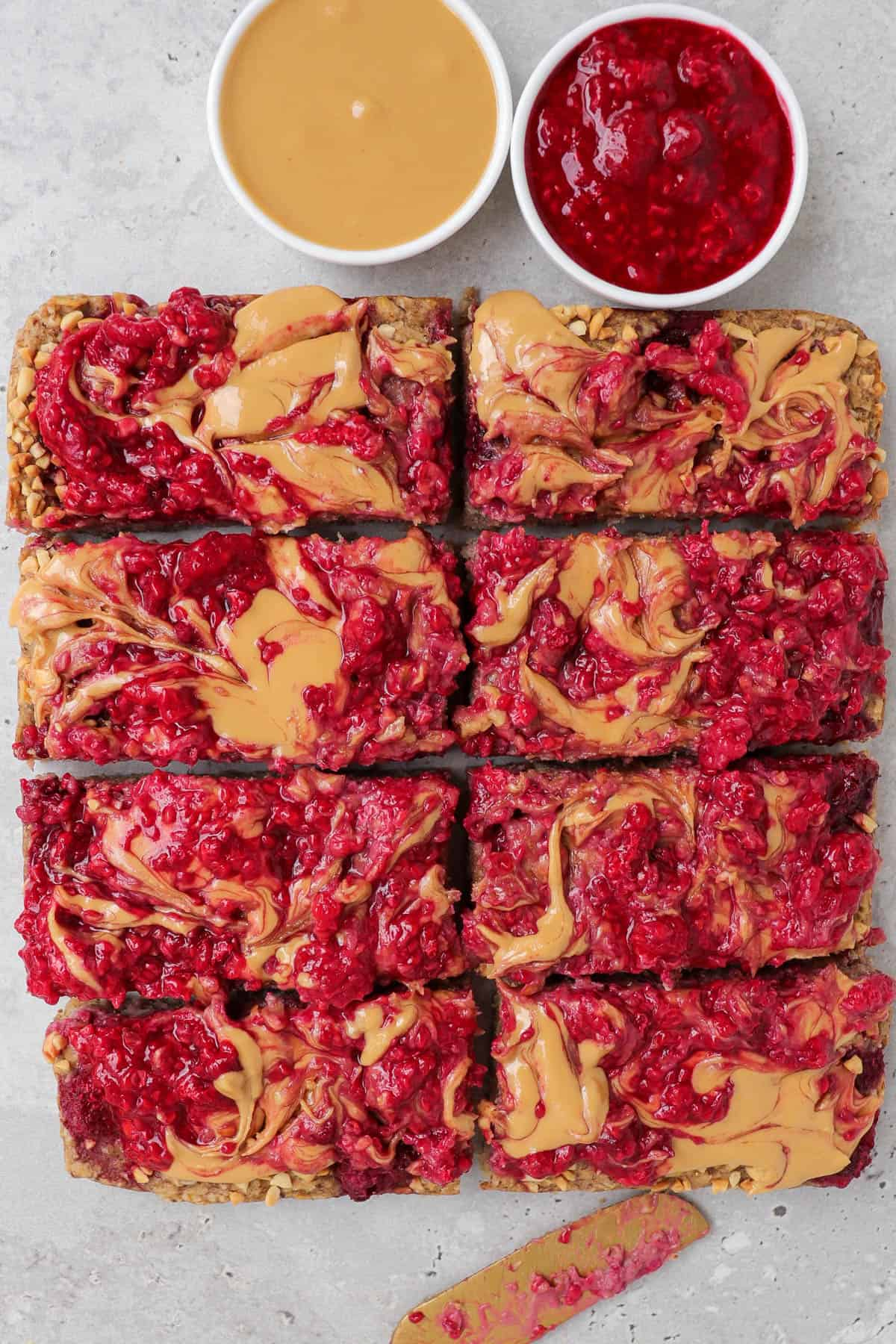 Peanut butter and jelly oatmeal cut up into bars. Small dish of peanut butter, mashed raspberries and gold knife on sides.