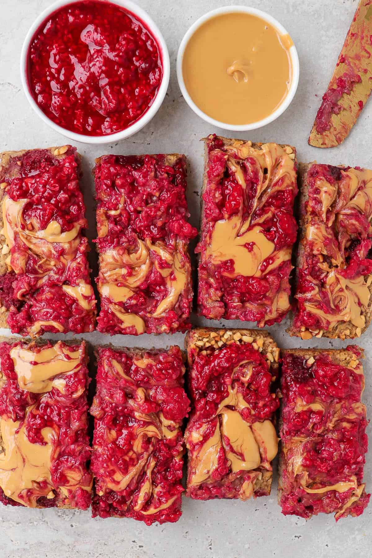 Pb&j oatmeal bars with small dish of peanut butter, mashed raspberries and gold knife above.