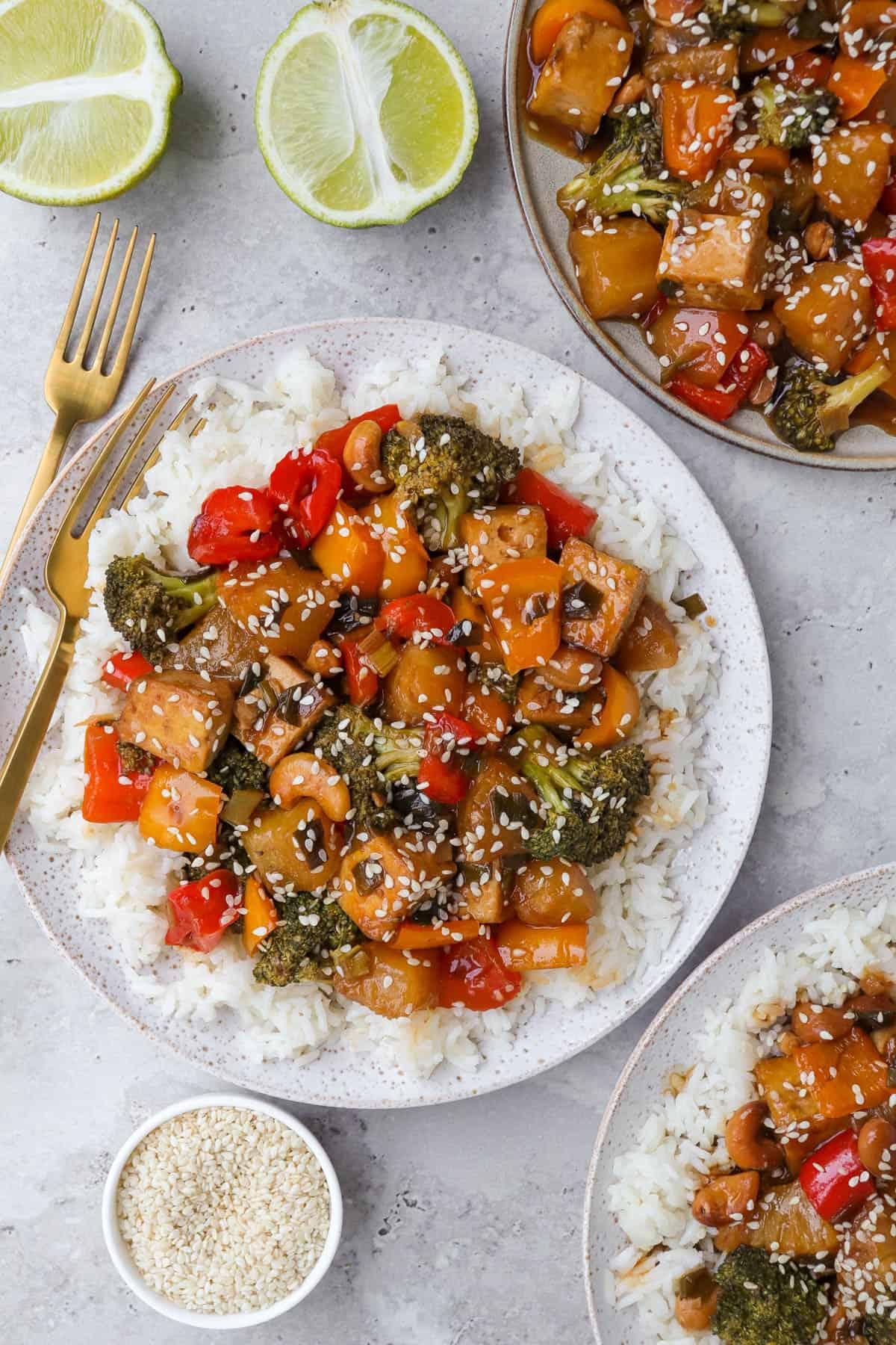 Pineapple tofu stir fry on three plates. Forks, limes and sesame seeds on sides.