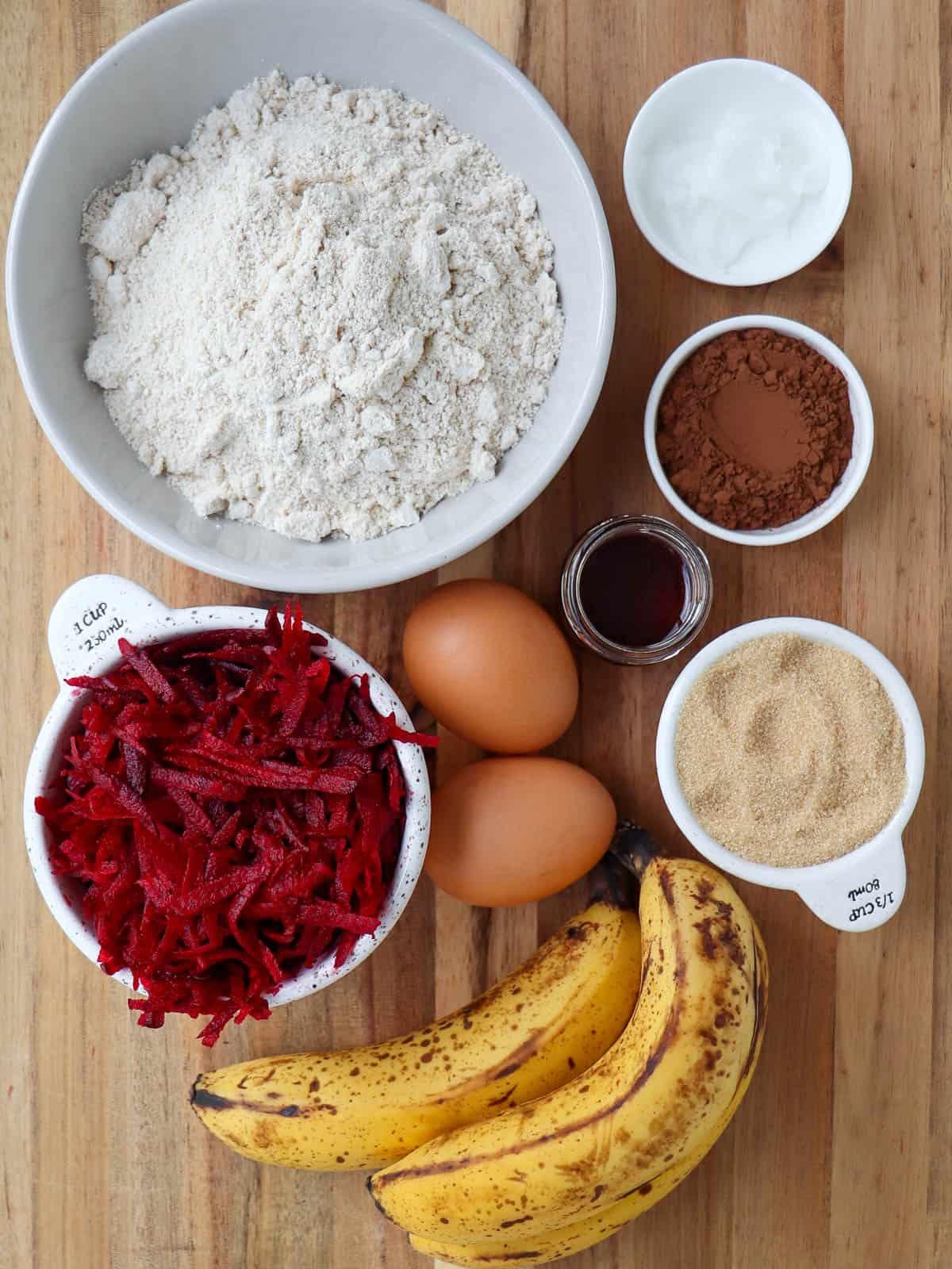 Red velvet cake ingredients on wooden board.