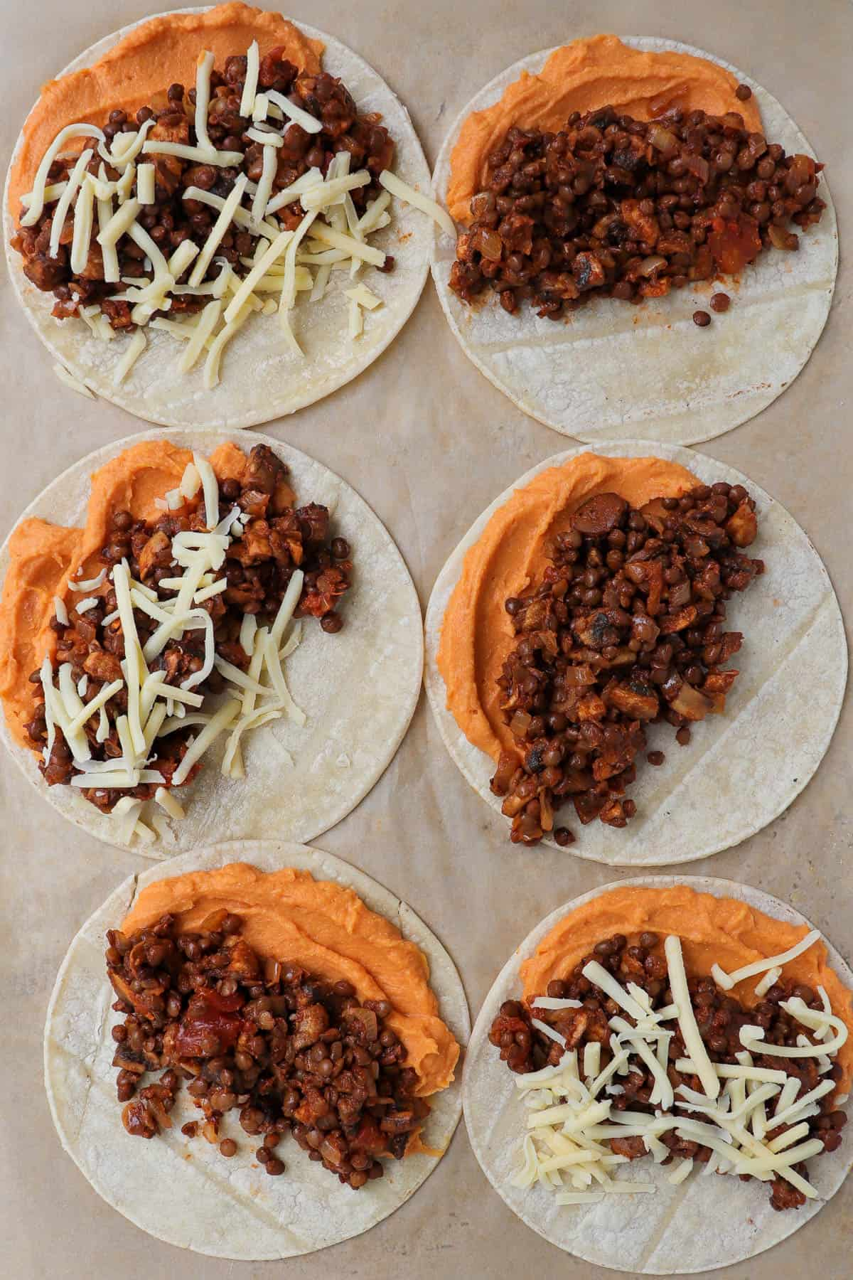 Tortillas topped with sweet potato mash, lentil filling and grated cheese.