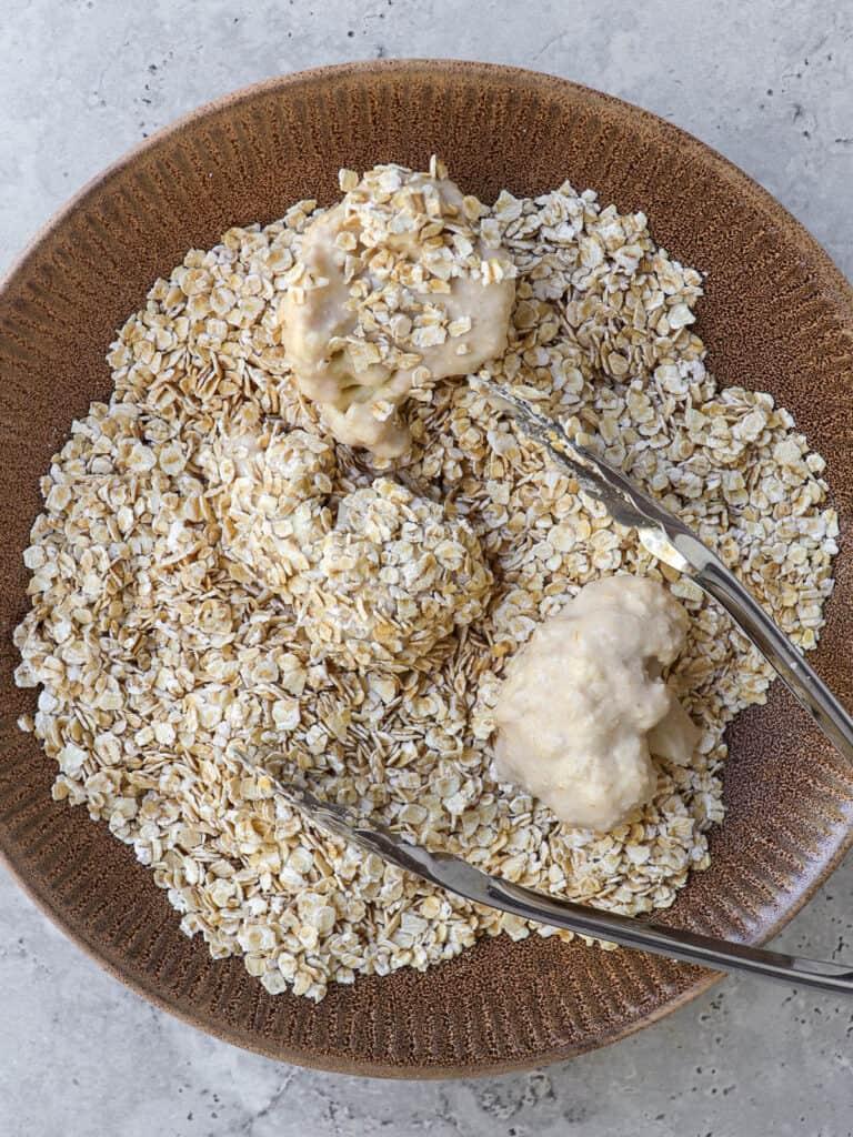 Cauliflower coated in oatmeal with tongs.
