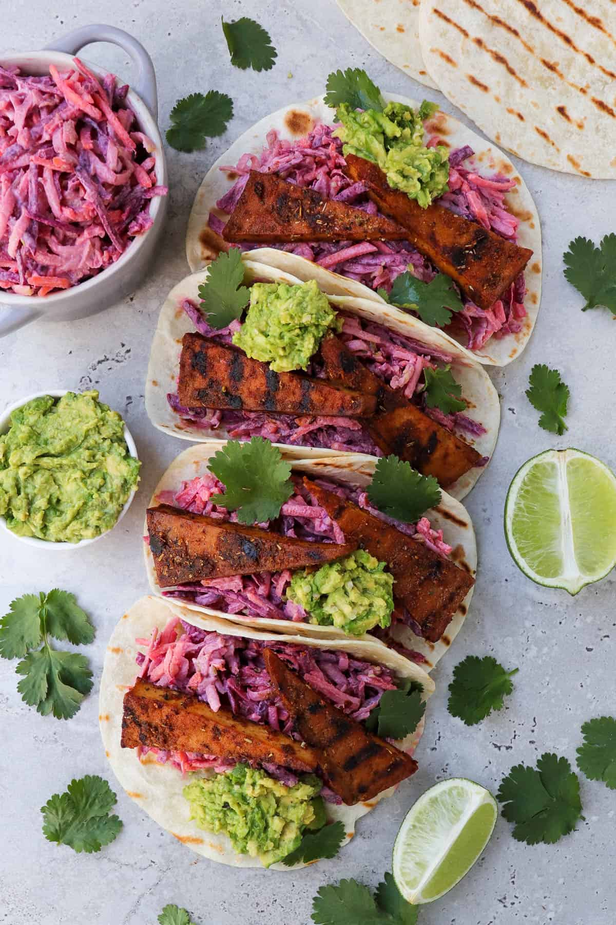 Top view of tofu tacos on angle. Coriander leaves, limes, avocado and slaw in a dish on the sides.