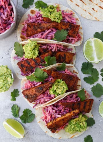 Top view of tofu tacos. Coriander leaves, limes, avocado and slaw on the sides.