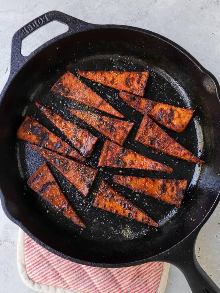 Blackened tofu in pan.