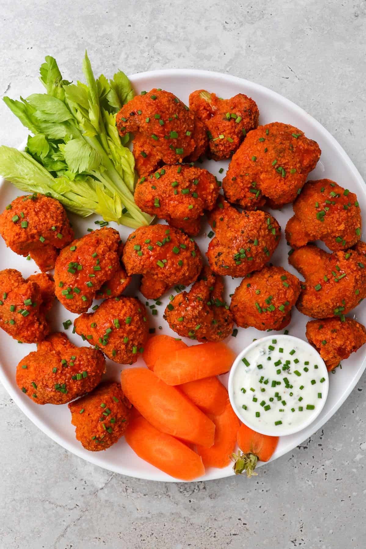 Buffalo broccoli wings on a plate with celery, carrots and ranch.