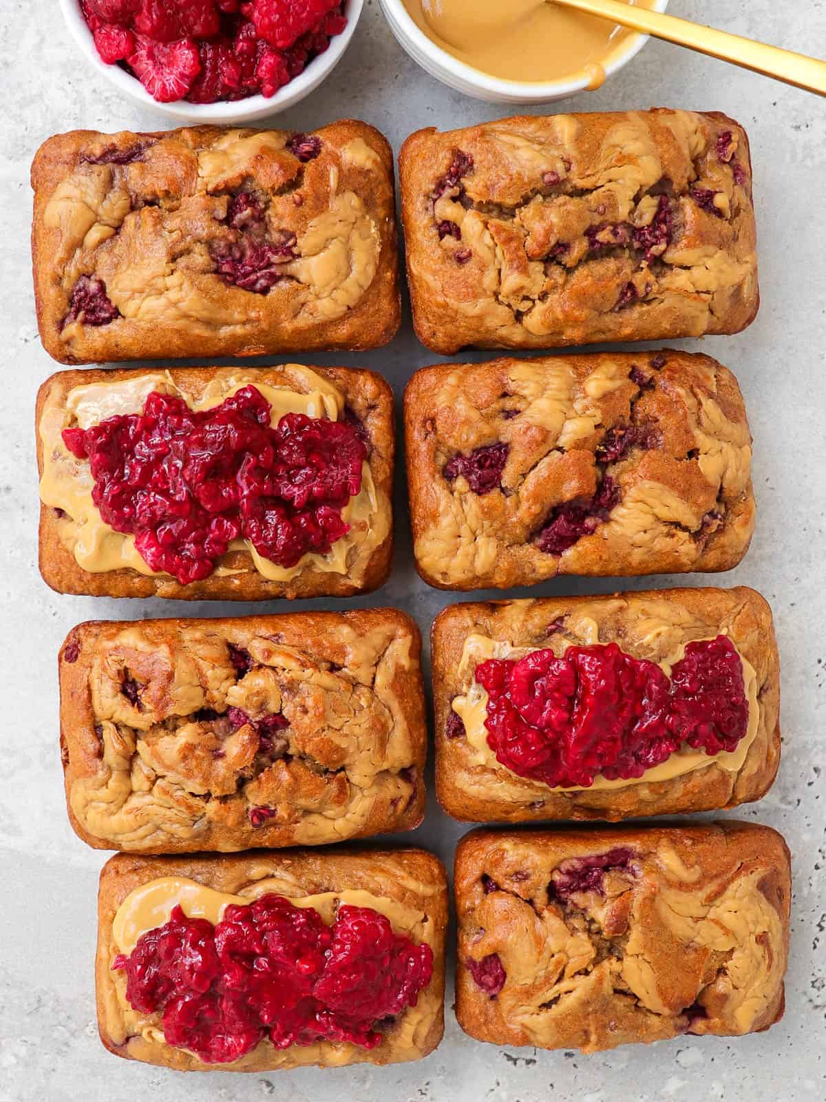 Some breads topped with extra peanut butter and mashed raspberries.